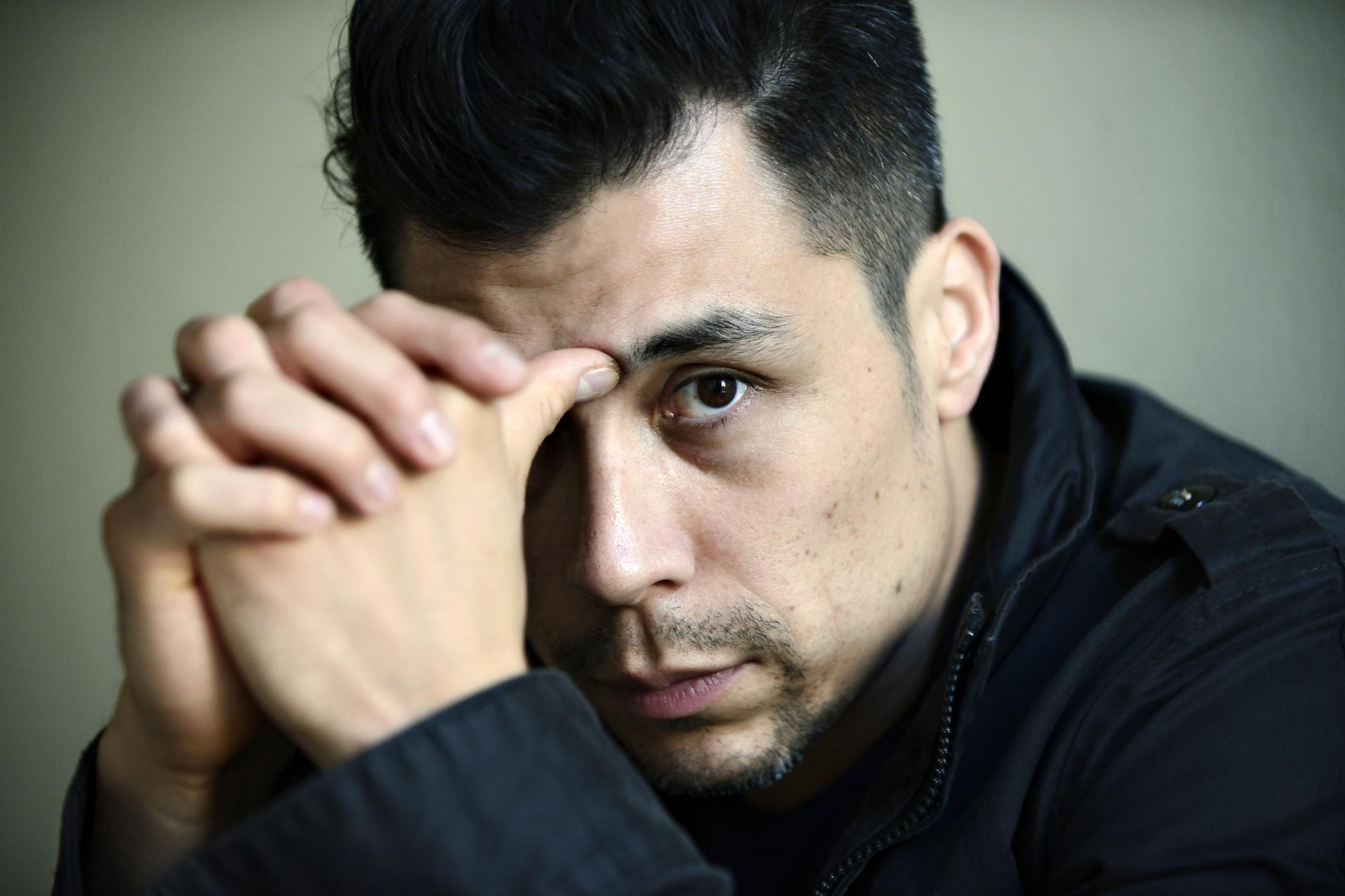 A light-skinned man poses with hands folded, thumb pressed against the bridge of his nose. He looks out at the viewer.