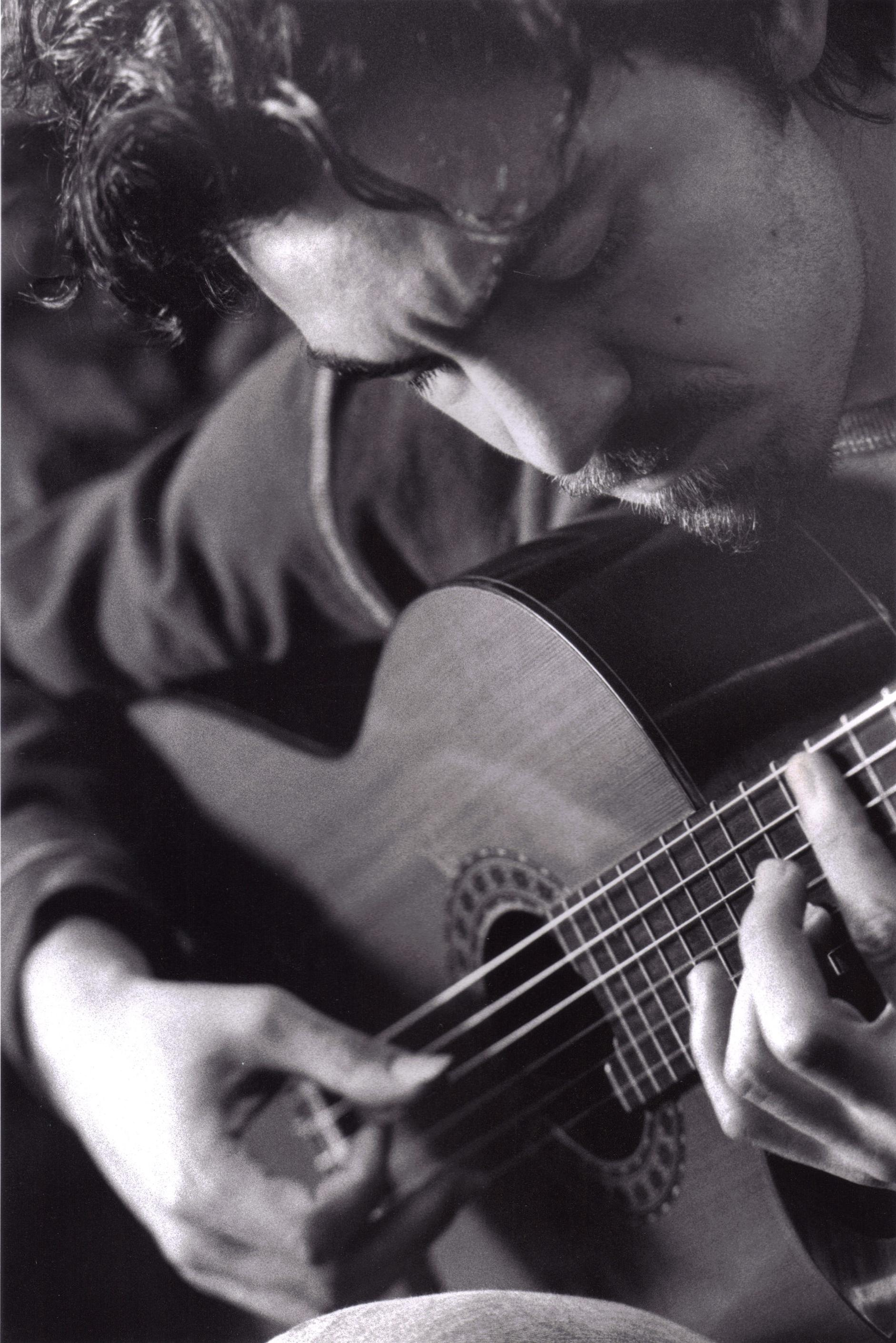 In this black-and-white portrait, a light-skinned male musician plays the guitar.