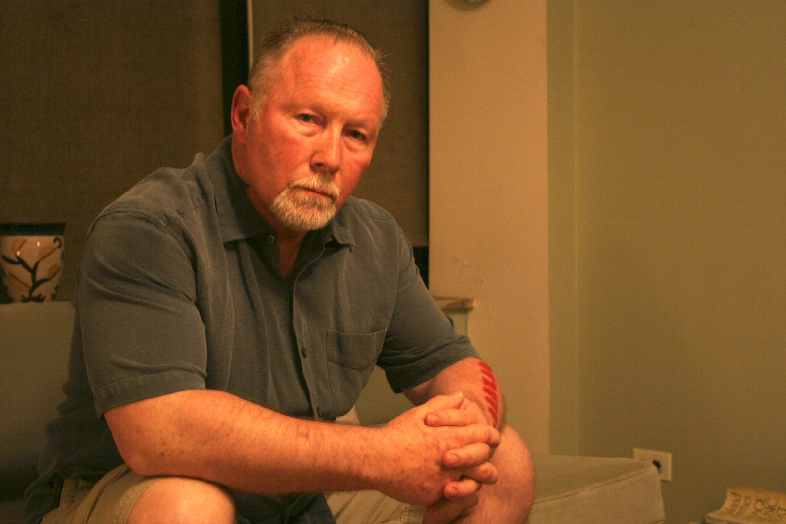 A muscular man with receding hairline and a gray goatee sits, hands folded, looking at the camera at the camera, expressionless.