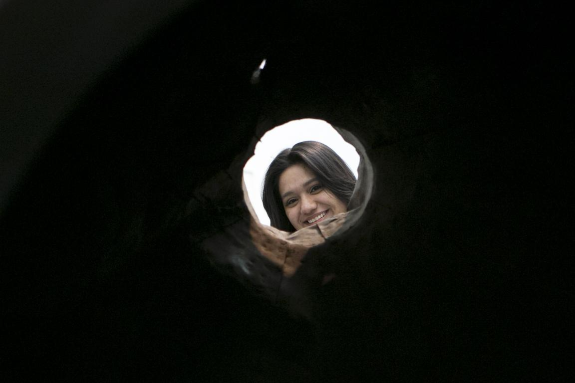 Pitch black environment pierced by a small hole, which leads to bright light and a woman's smiling face