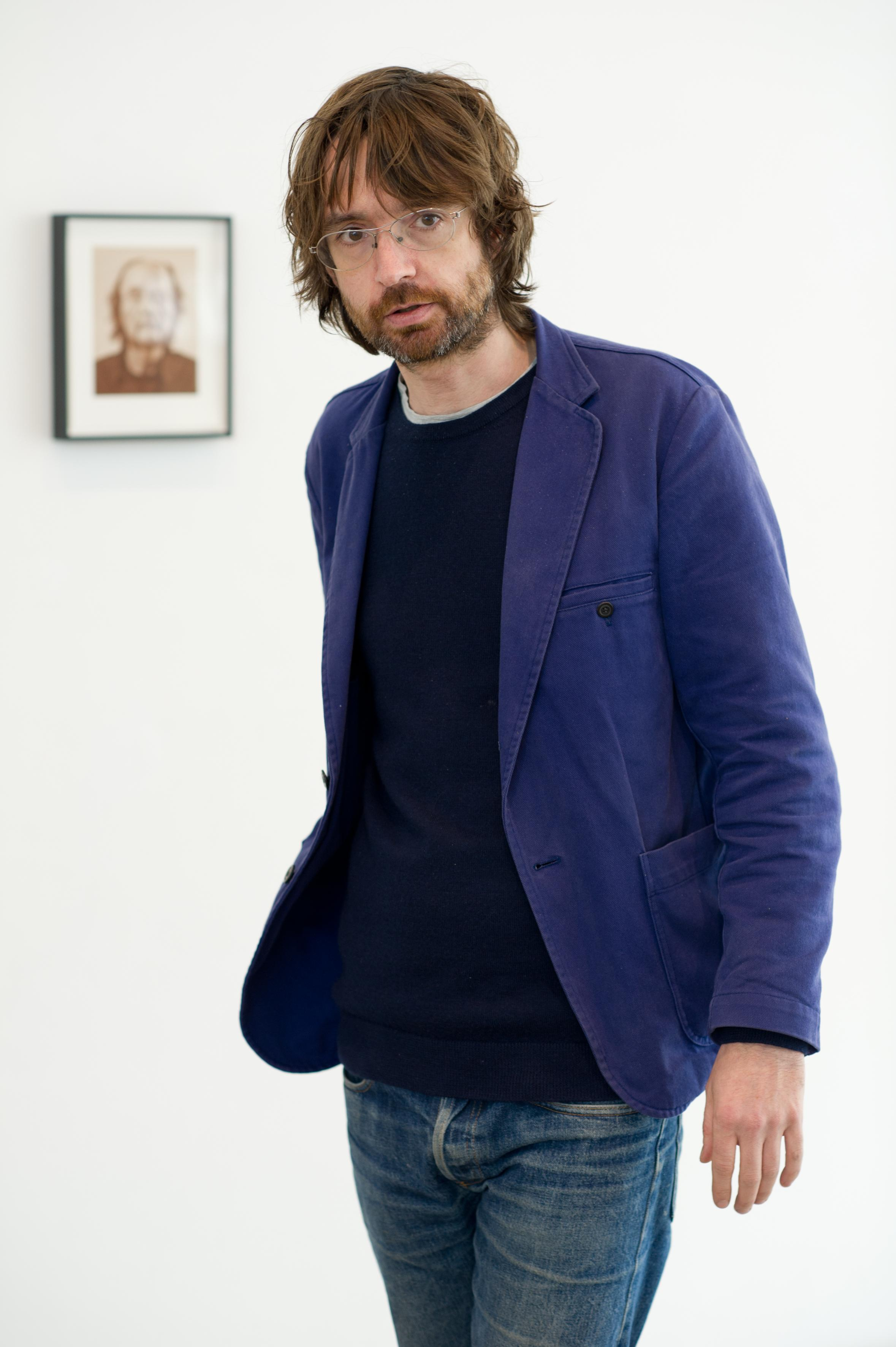 Photograph of a shaggy haired man, wearing glasses and a bright blue suit jacket, standing in front of a framed portrait hung on the wall