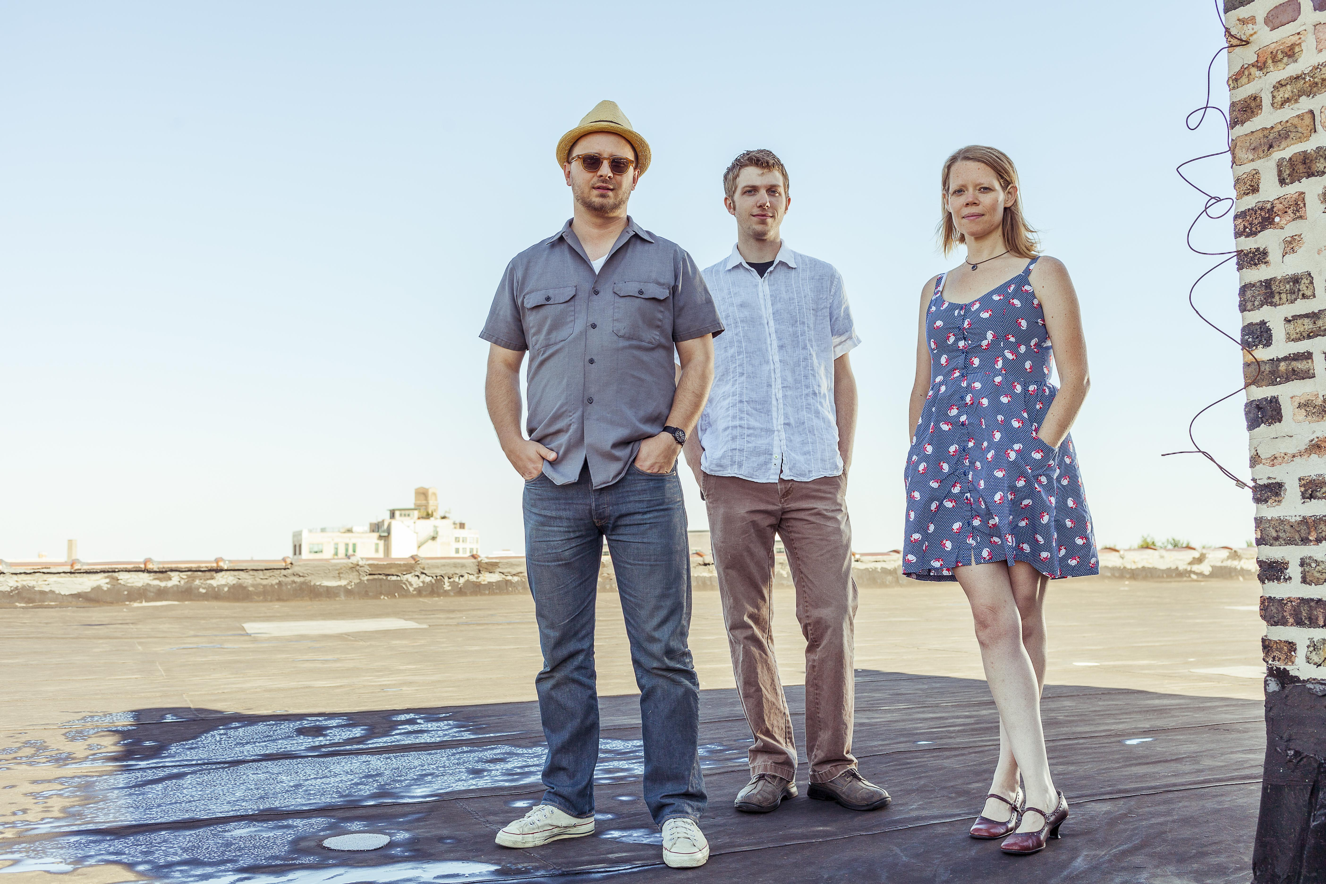 On a sunny day, two men and one woman stand in a shadow cast upon a rooftop.