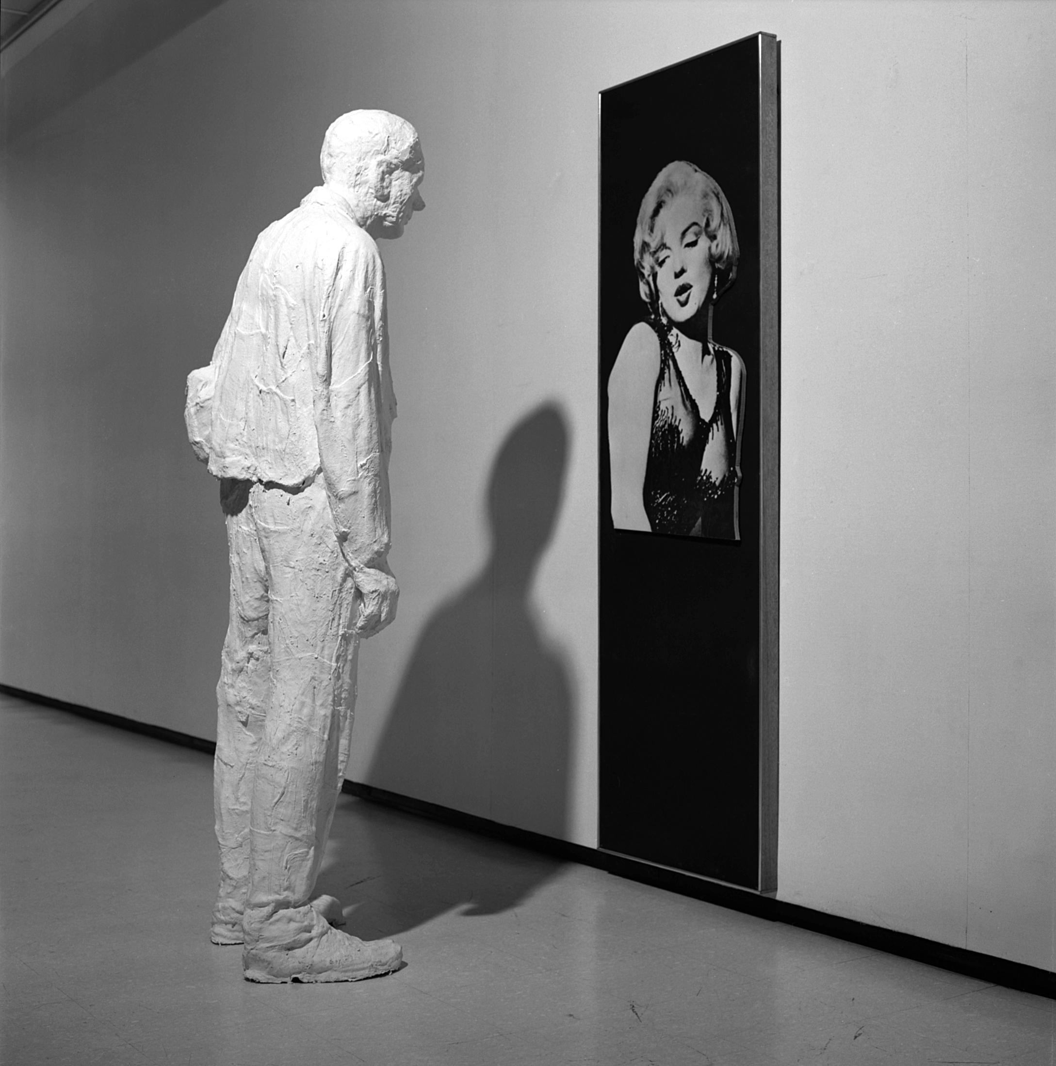 A black-and-white photo shows a white plaster figure of a man in work clothes stands facing a large, vertical, rectangular photograph of an extremely attractive blond woman.
