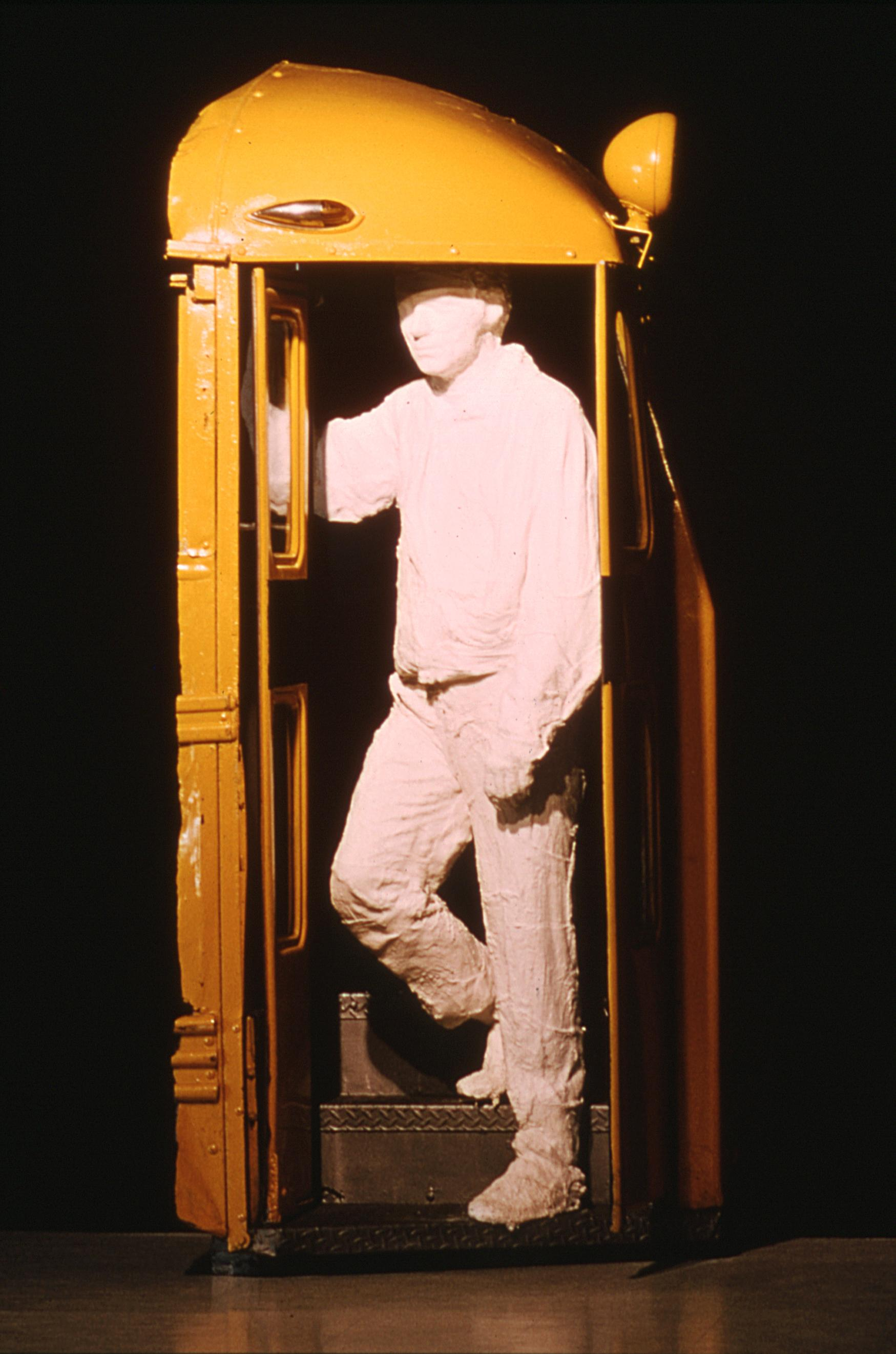 A life-size, white plaster cast of a man in work clothes appears to descend the front step of a yellow school bus.
