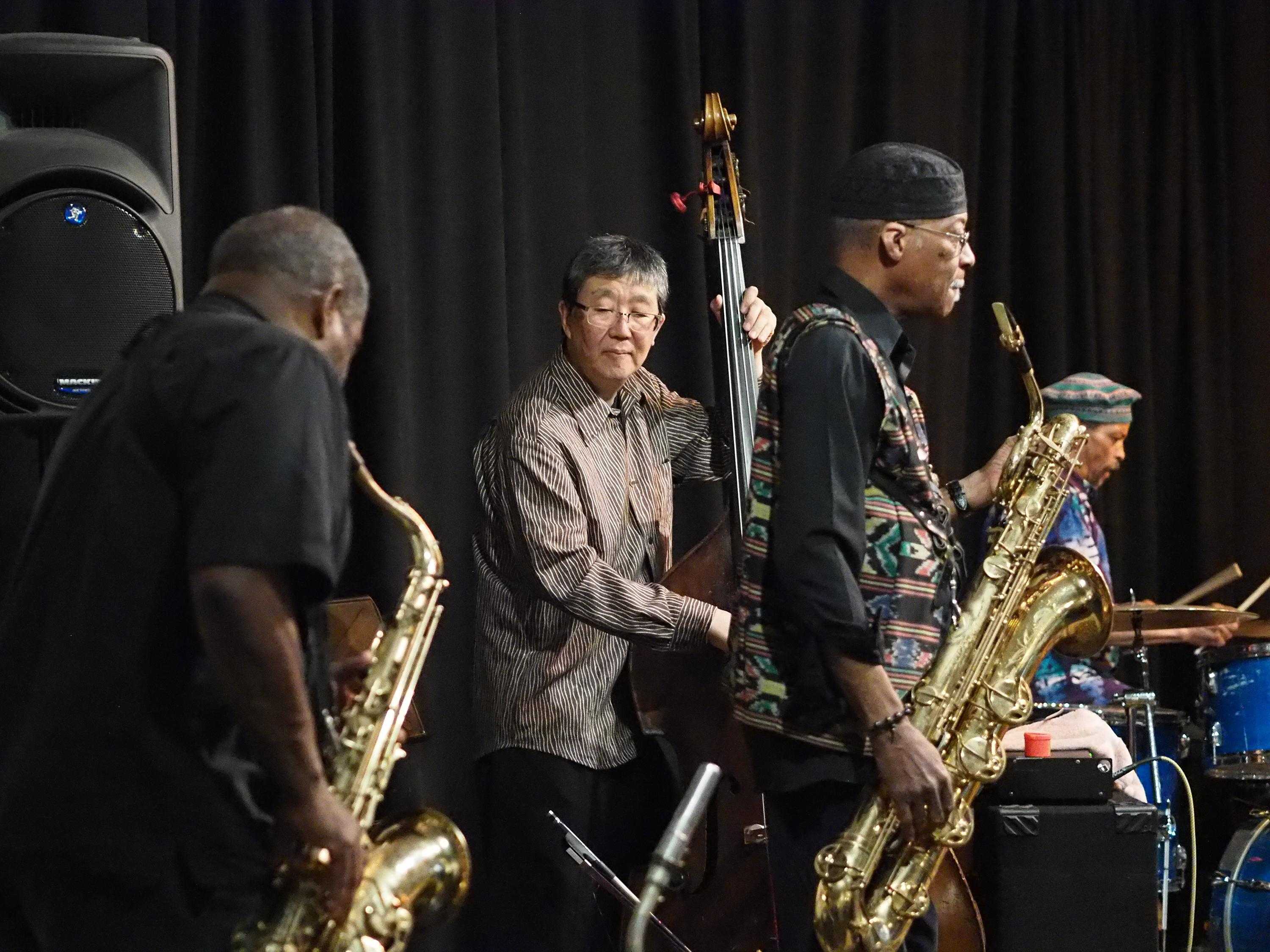 Jazz musicians performing on alto and tenor saxophones, string bass, and drums