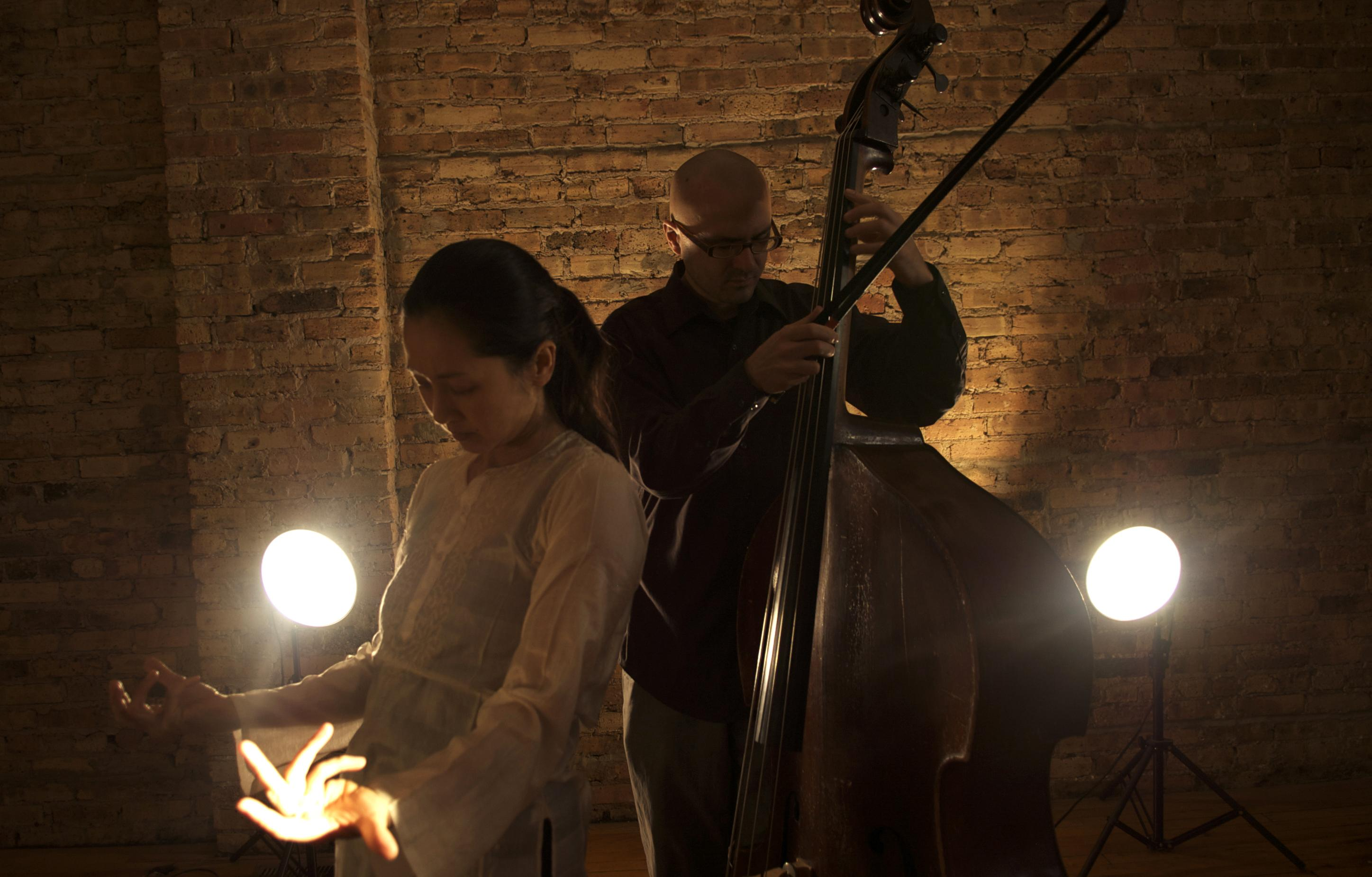 A woman and man in a dark room are backlit by two spotlights. He plays a string bass while she gestures with both arms, empty handed and fingers curled.