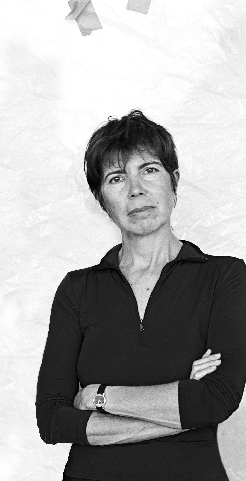 Black-and-white portrait of a short-haired woman, arms crossed, in a black zippered top