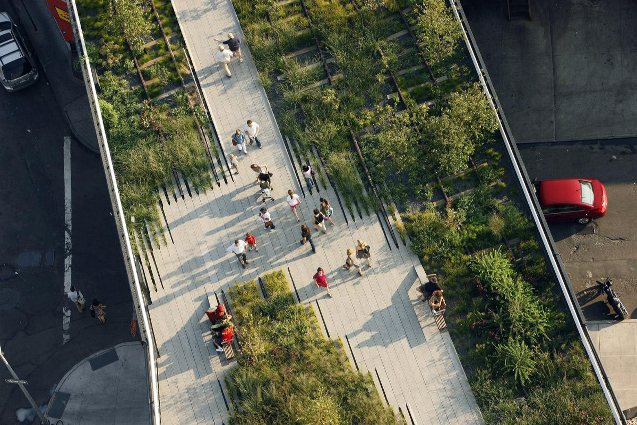 Aerial view of a linear, raised boardwalk with greenery and a handful of people