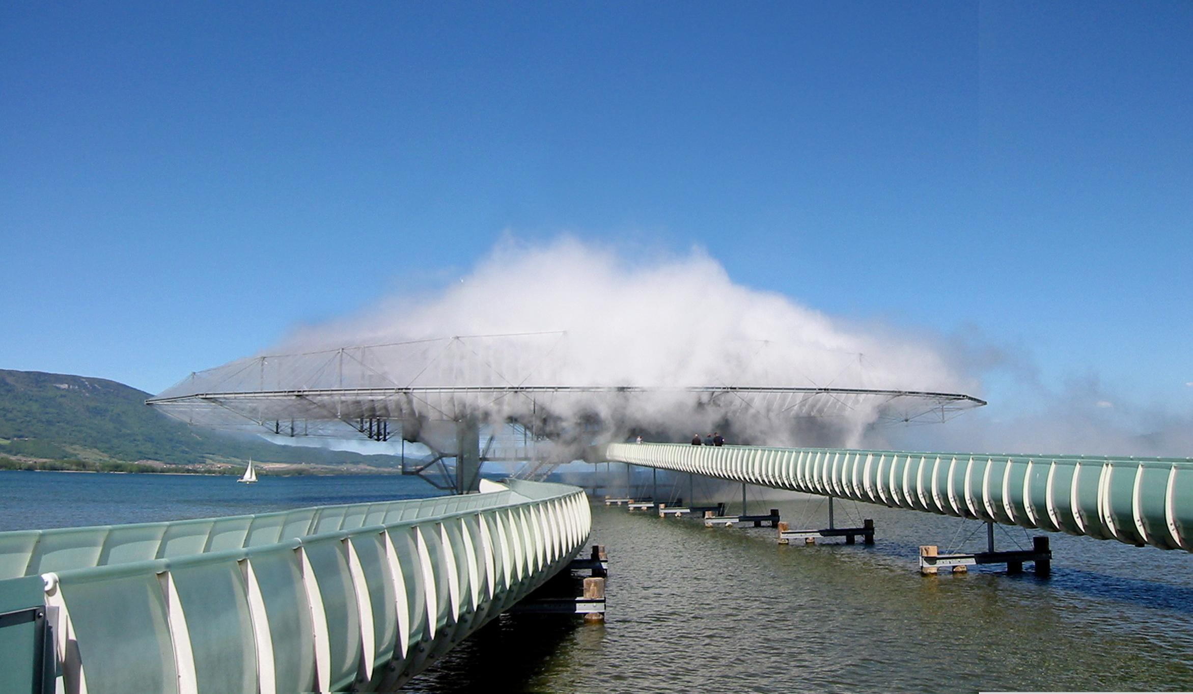 Two floating bridges lead to a saucer-shaped building, engulfed by mist, in the middle of a lake.