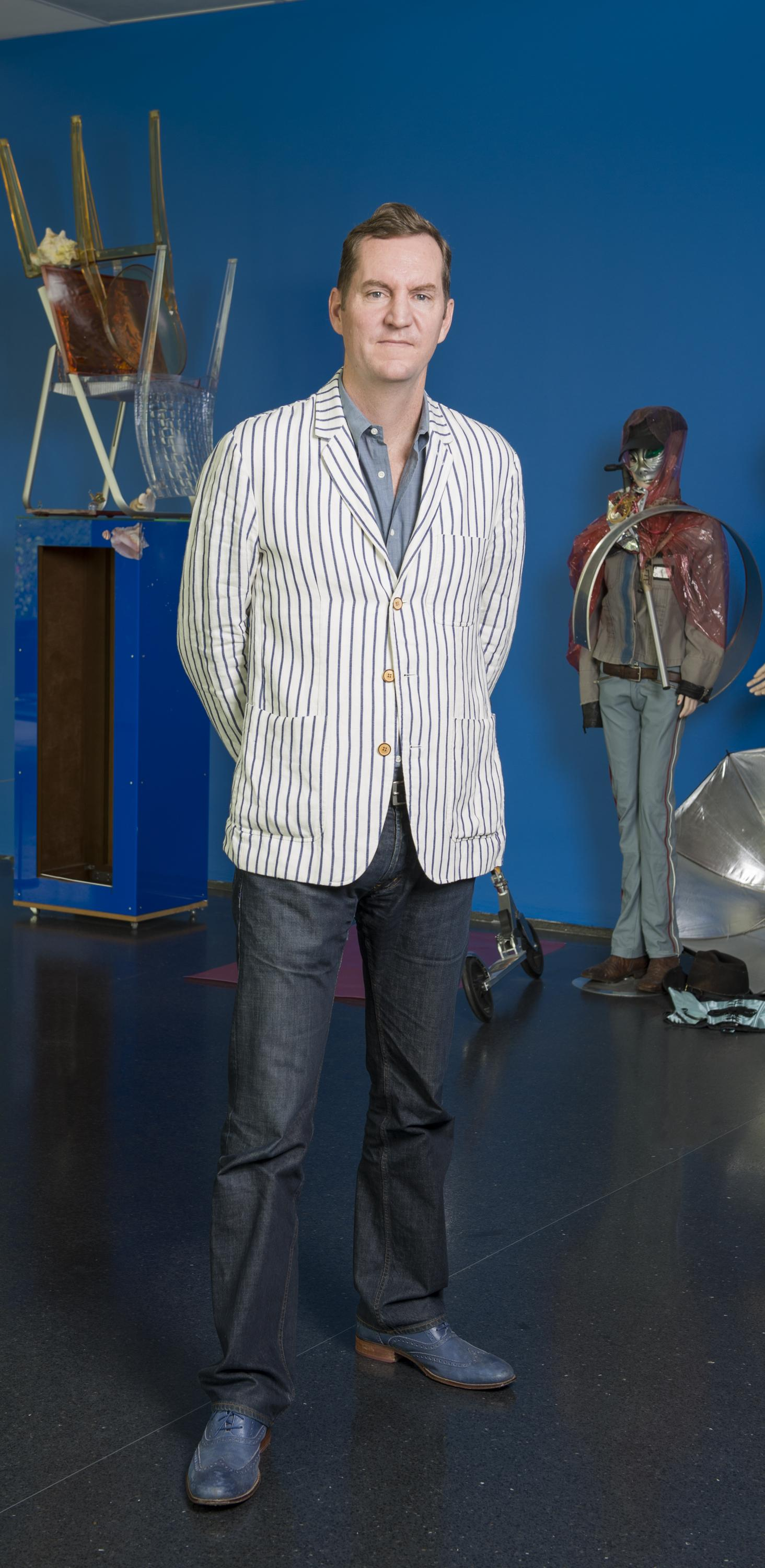 Photograph of a man in a pin-striped blazer standing in front of several Isa Genzken sculptures