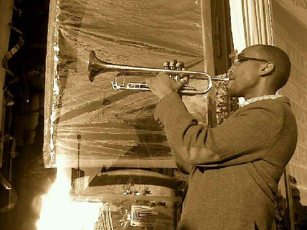 Sepia portrait of a man in a suit jacket with elbow patches playing the trumpet