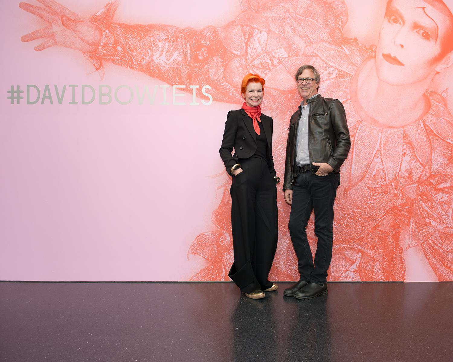 A woman and man posing at the entrance of the exhibition *David Bowie Is*.