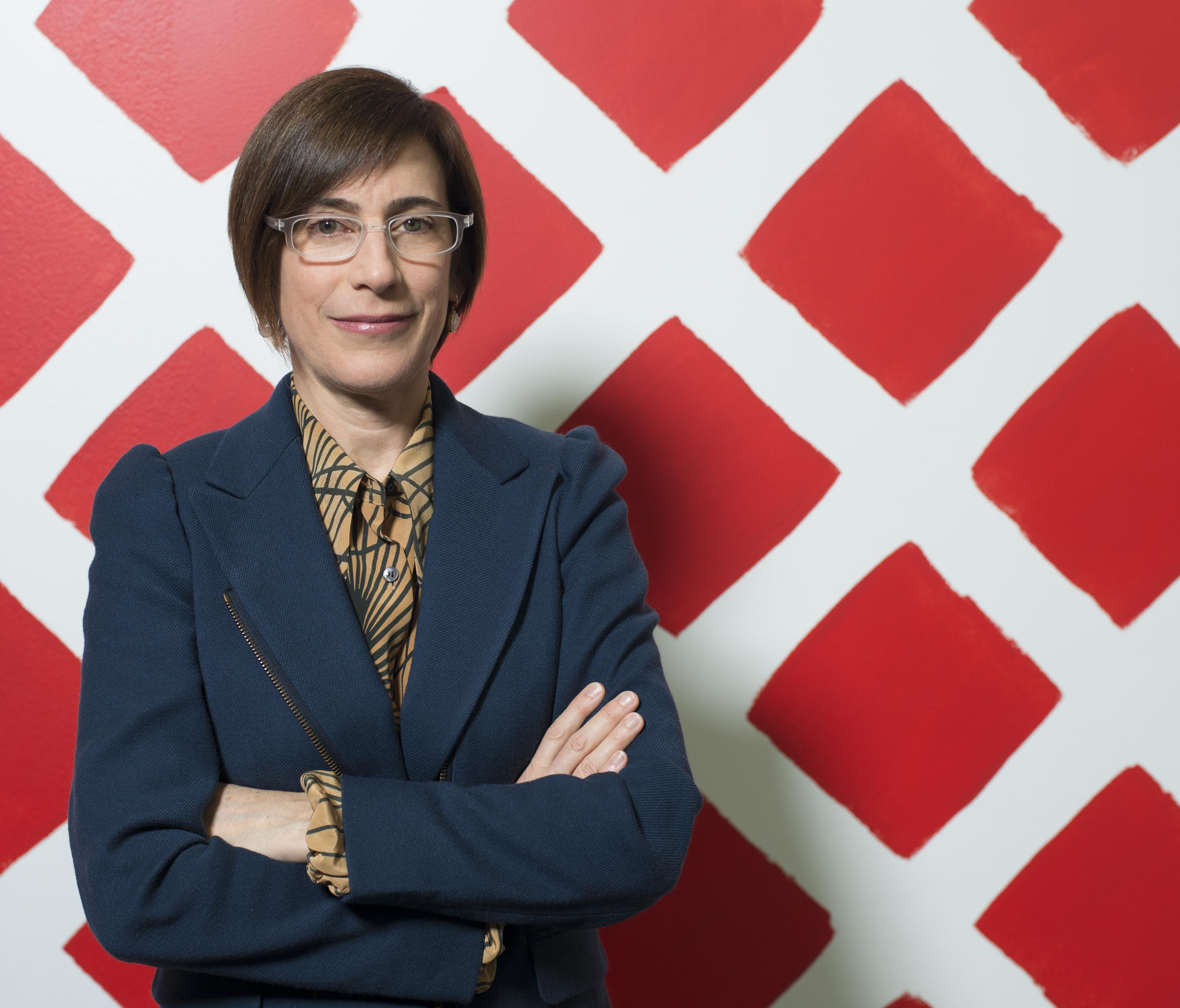 Portrait of Museum of Contemporary Art Chicago Director Madeleine Grynsztejn, wearing a blue blazer and clear plastic glasses. She stands in front of Martin Creed's wall painting, Work No. 798, which looks like a series of red diamonds painted directly on the wall.