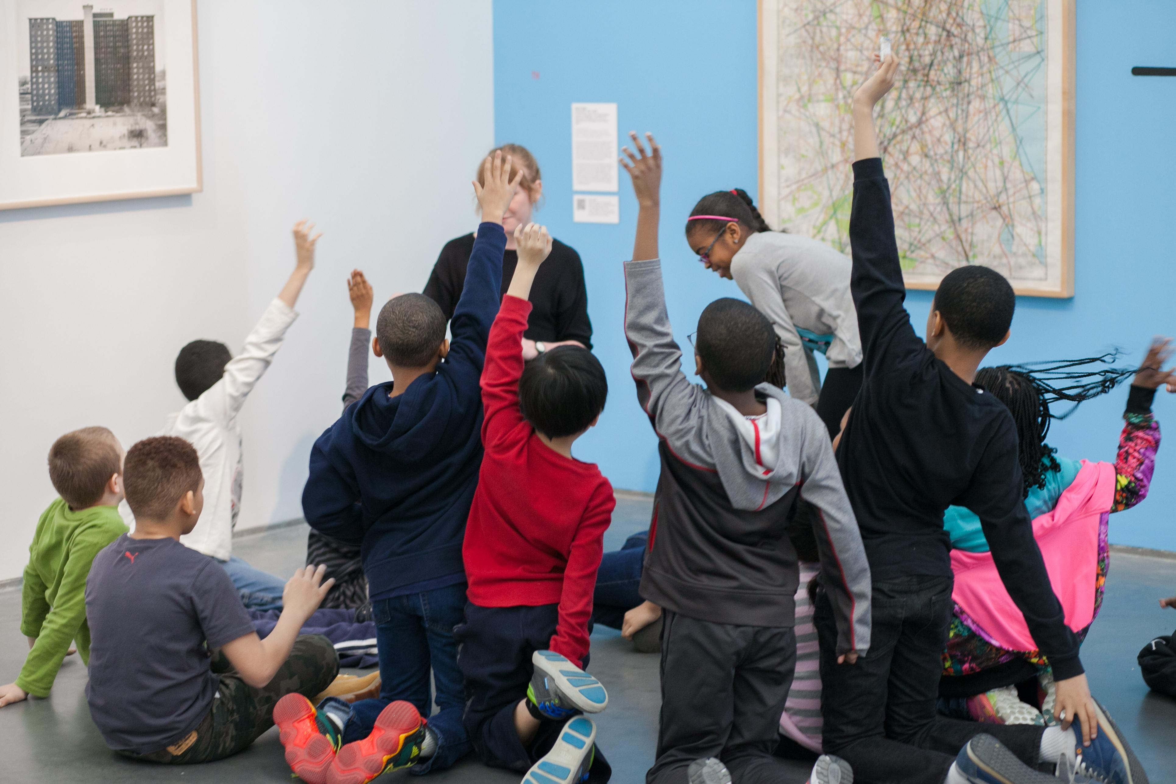 Group of children sitting and kneeling in a gallery raise hands as if to answer a question
