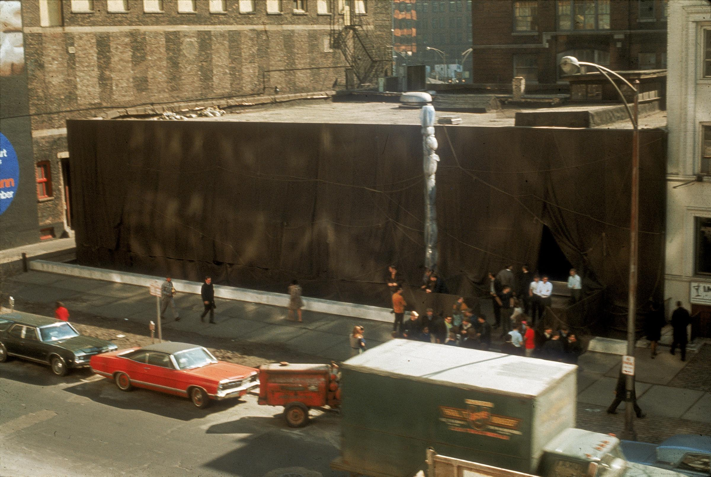 A street view photograph with people on the sidewalk looking at a building wrapped in fabric; cars are parked along the street in the foreground