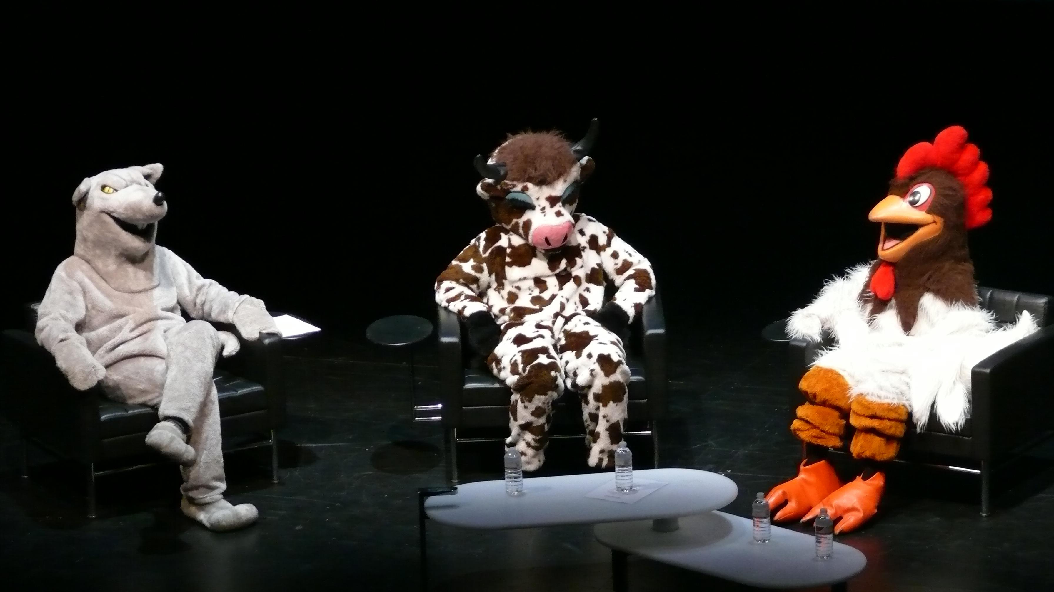 Three people dressed in animal costumes—a rat, a cow, and a chicken—sit on a stage.