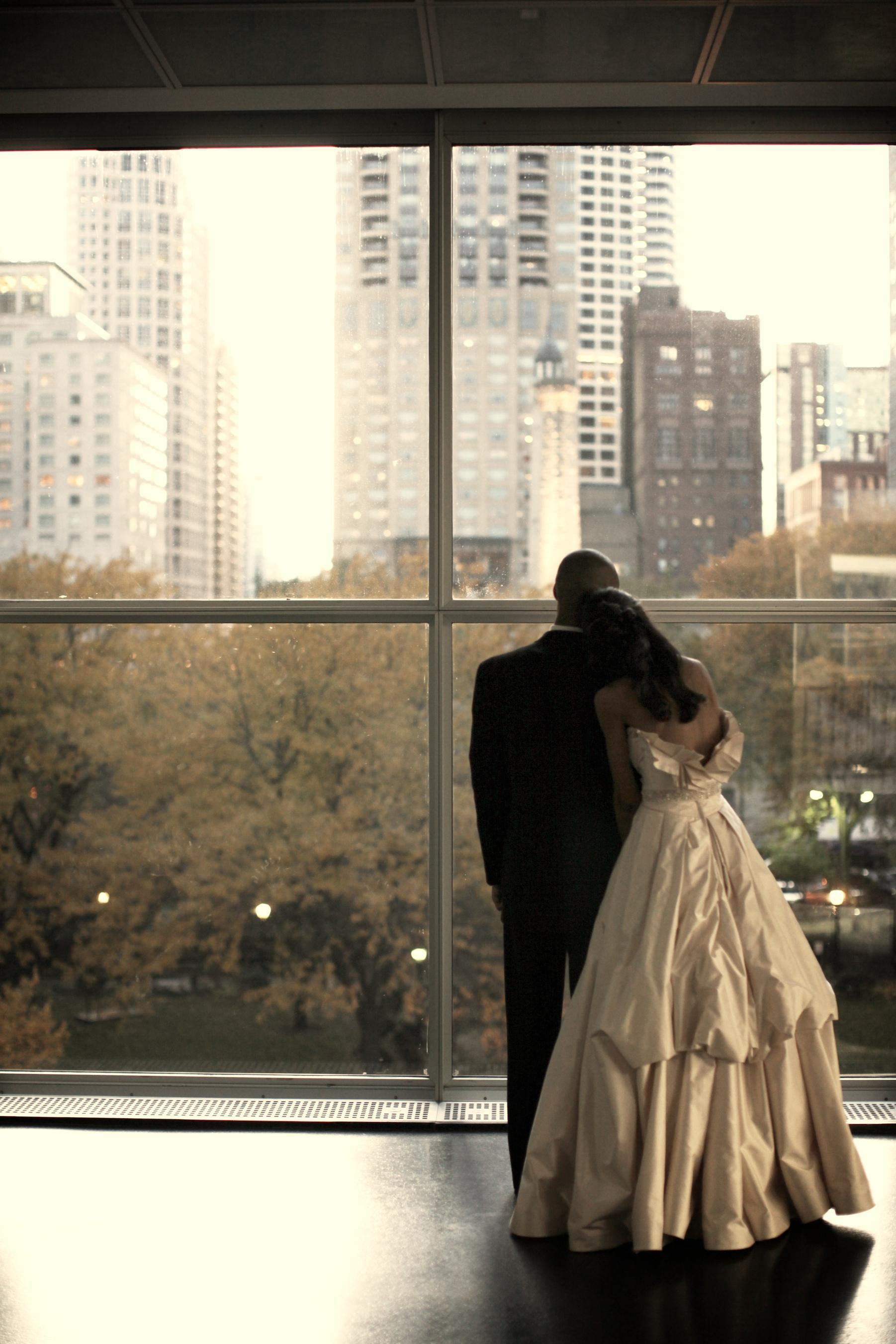 A bride and groom embrace while looking at trees and cityscape through the MCA's fourth floor windows.