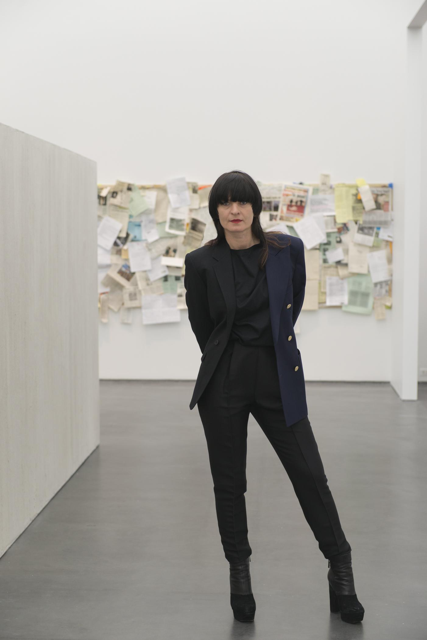 Portrait of a woman with long brown hair, blunt bangs, red lipstick and dressed in black standing in an exhibition at the MCA.