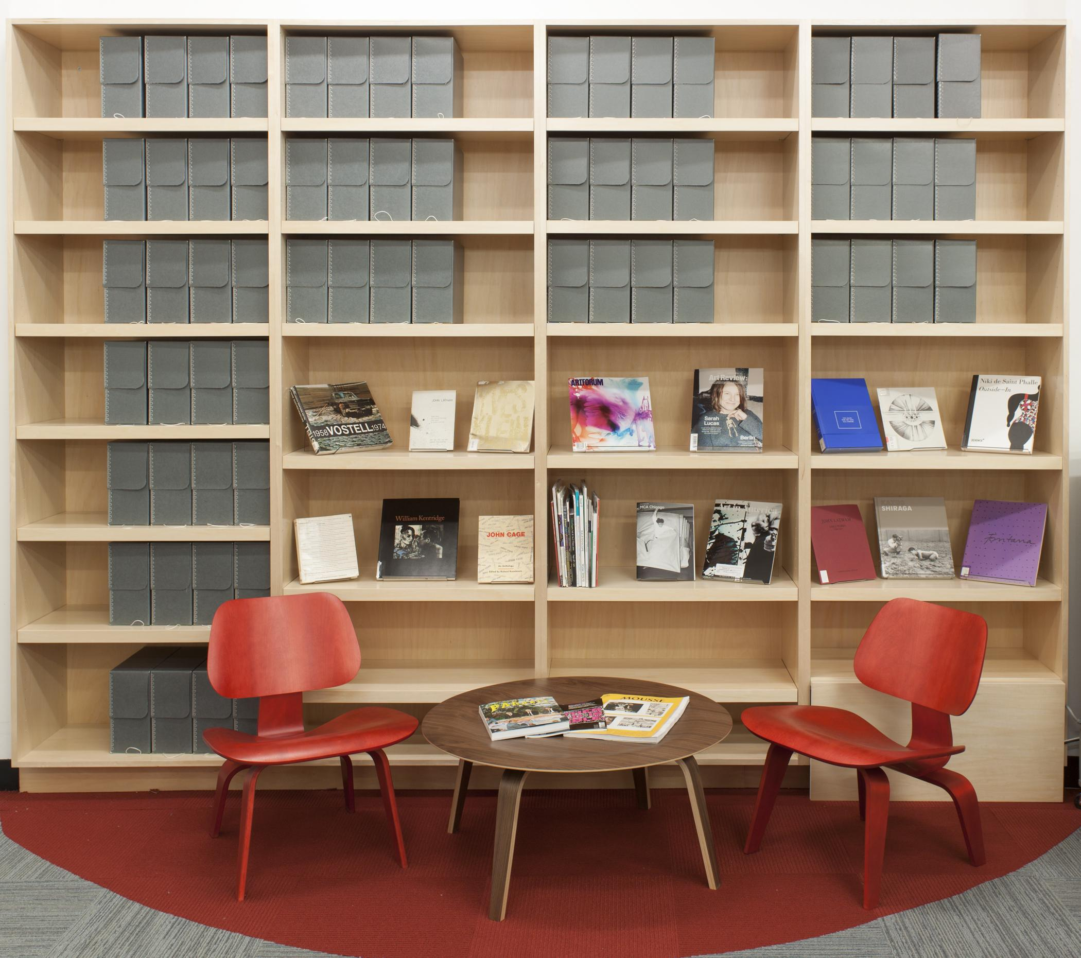 A side table and two chairs in front of gridded bookshelf with books and archival boxes on display