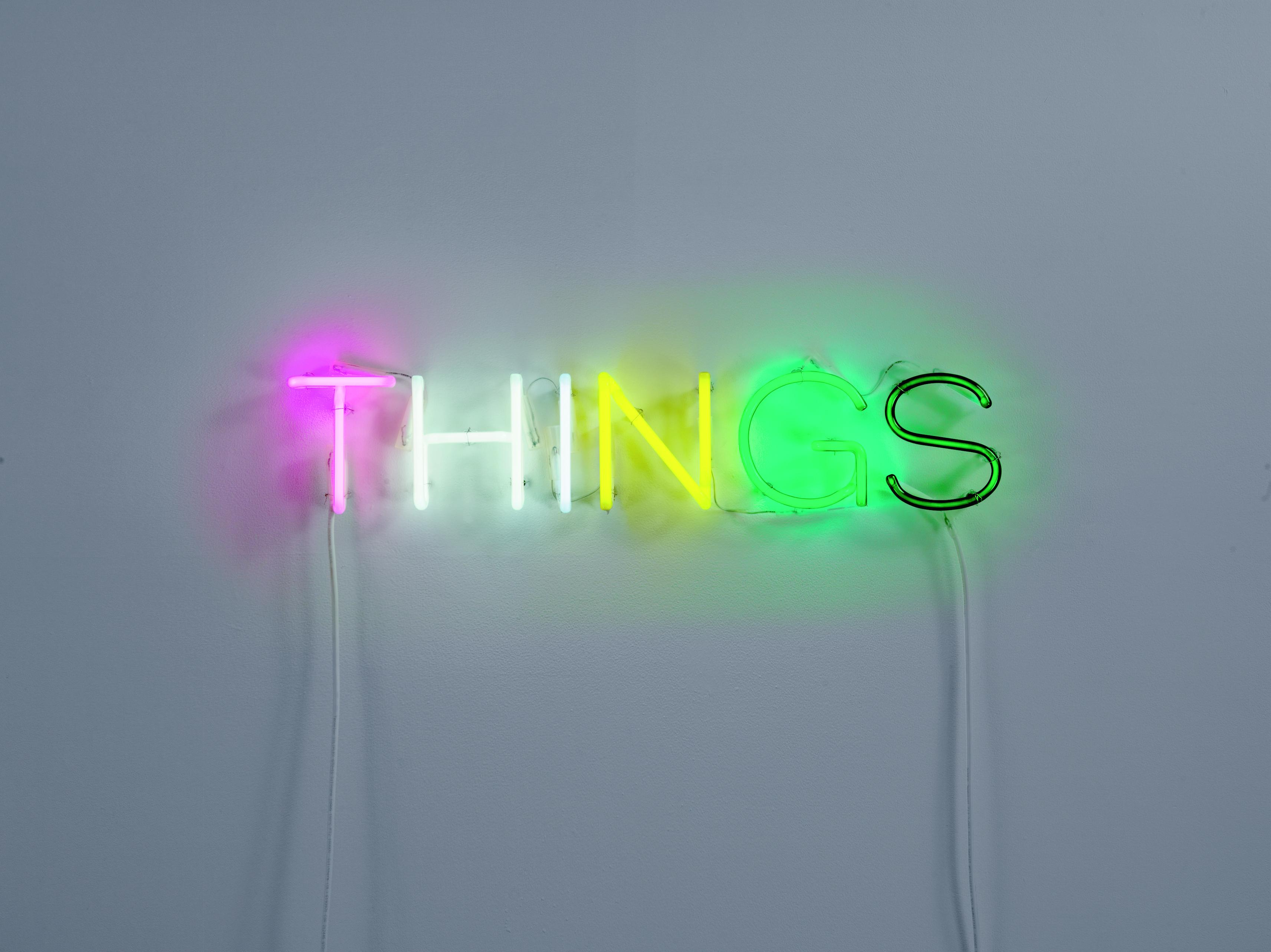 """A glowing neon-light sculpture spells out the word """"THINGS."""""""