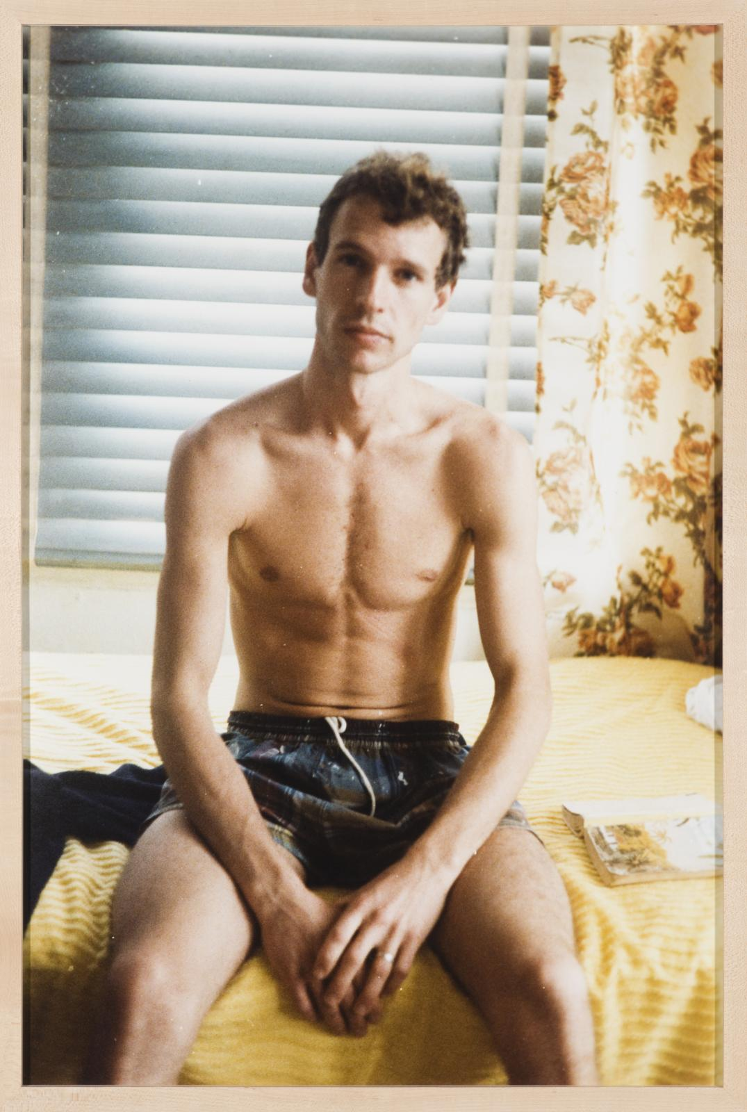 A topless, light-skinned man sits on a bed in a swimming suit. His head tilts just slightly to his left as he looks directly at the viewer.