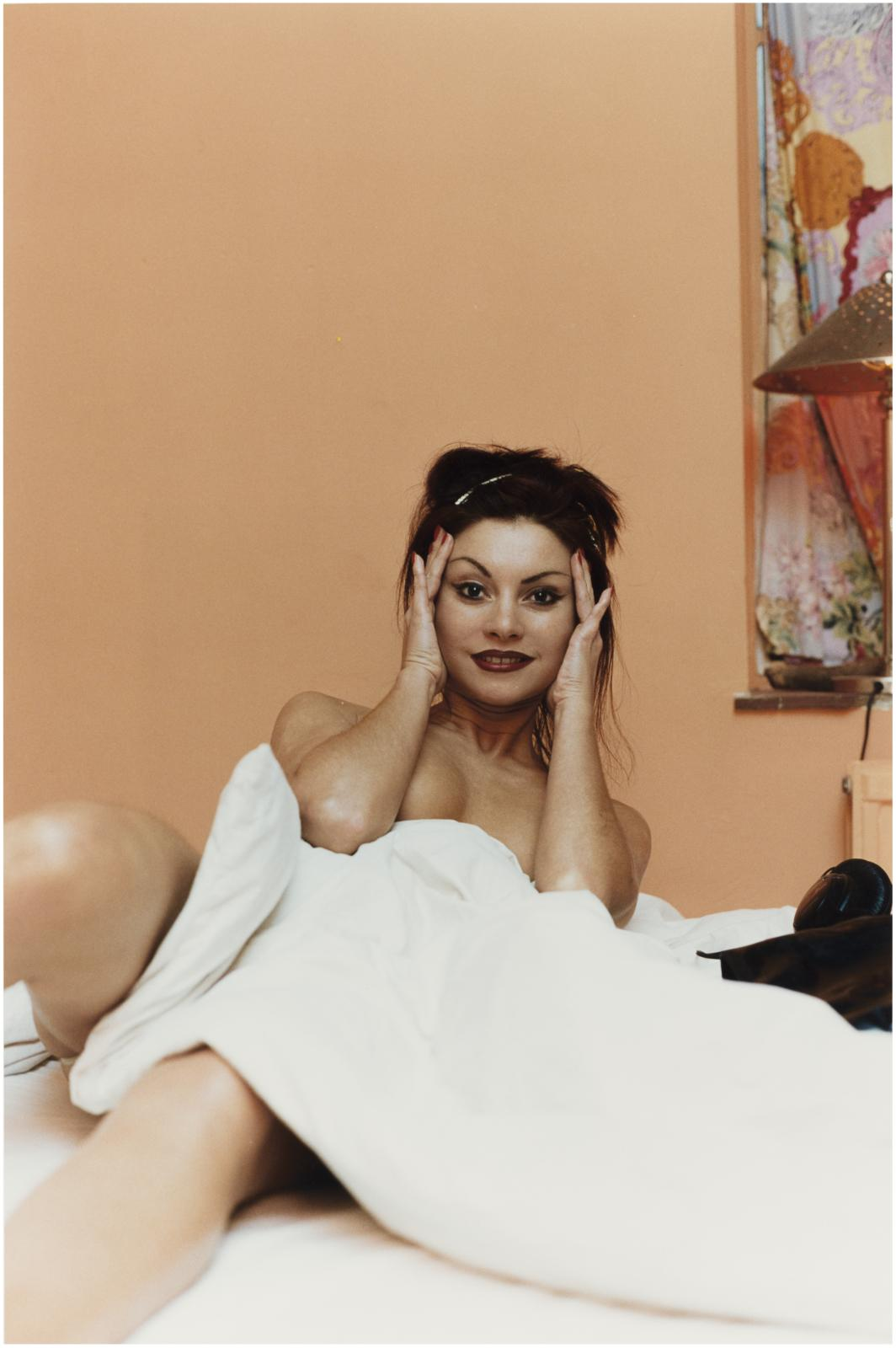 A nude adult with long dark hair, arched eyebrows, and dark lipstick holds their hands up to the sides of their face and looks into the camera. They are leaning back toward a peach-colored wall, and their torso is obscured by a white bedsheet.