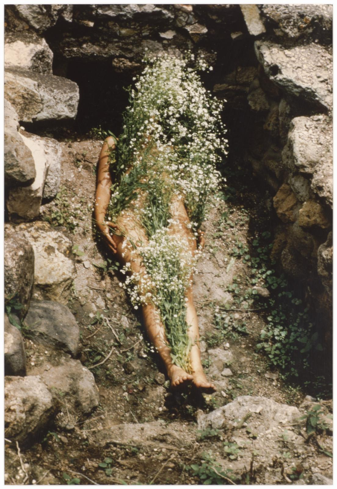 A person lays down in a stone-lined grave with flowers covering their body.