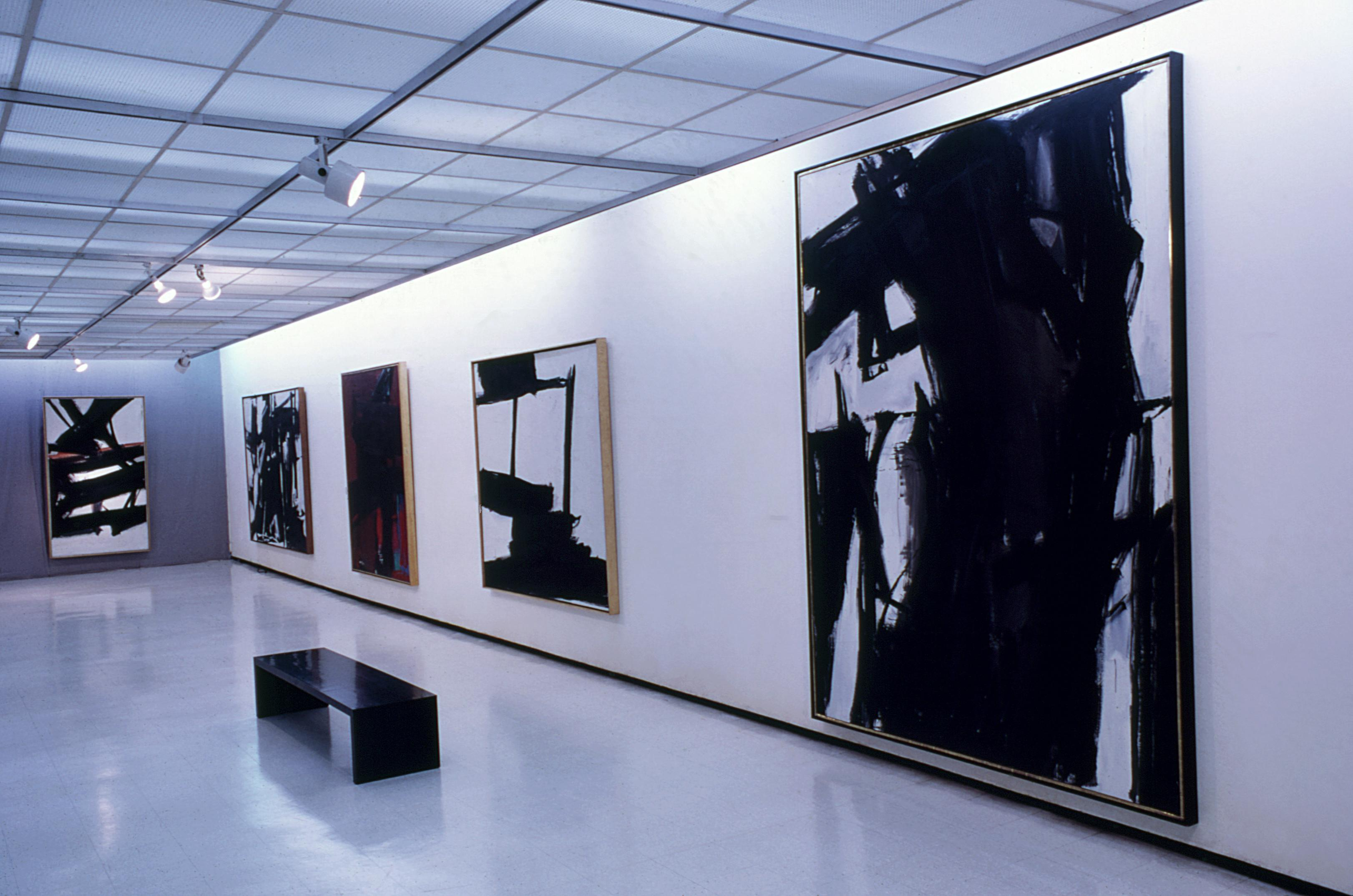 Five large paintings, predominately black and white, hang along a gallery wall.