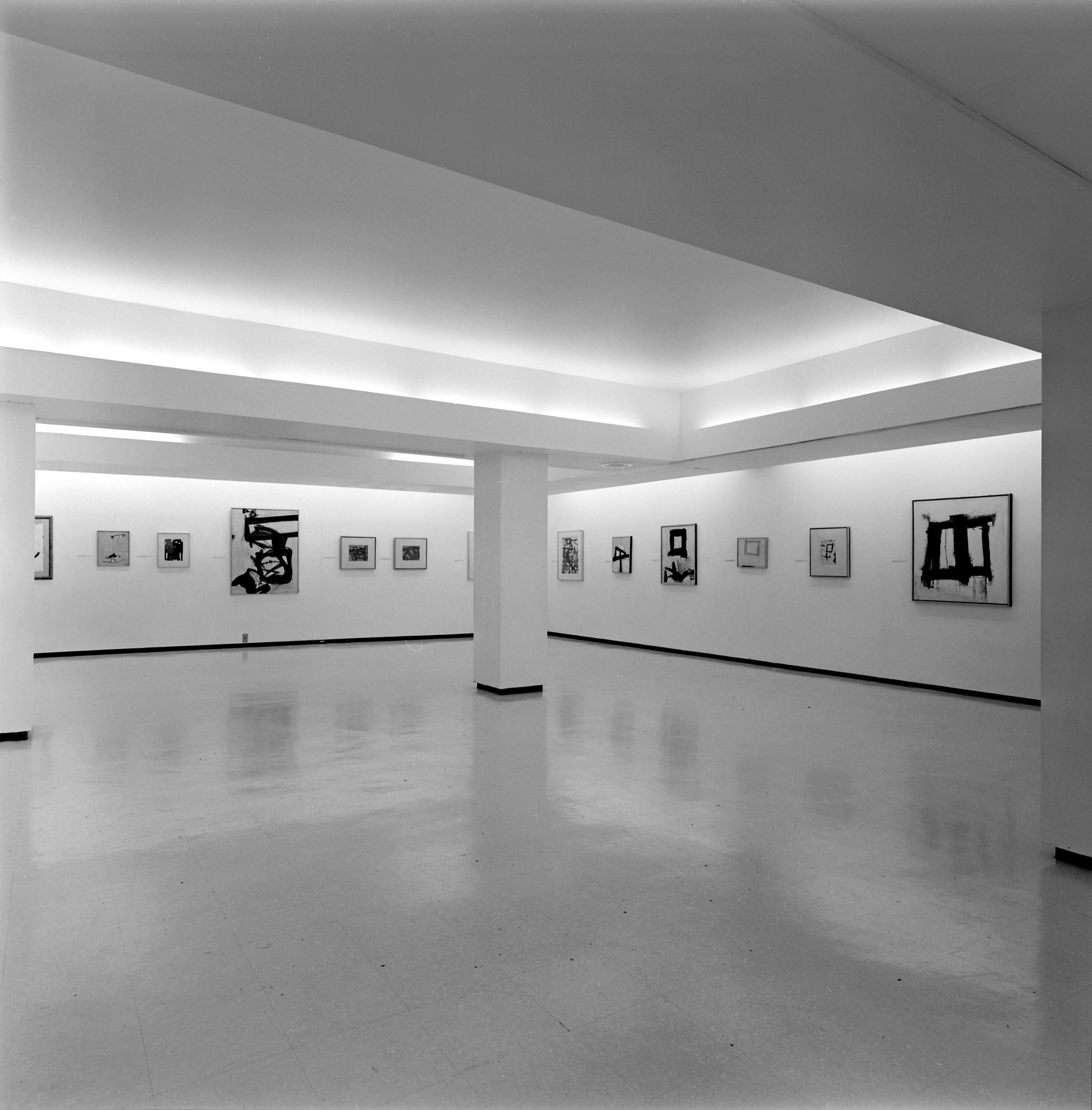 Many small black and white paintings hang along a gallery wall.