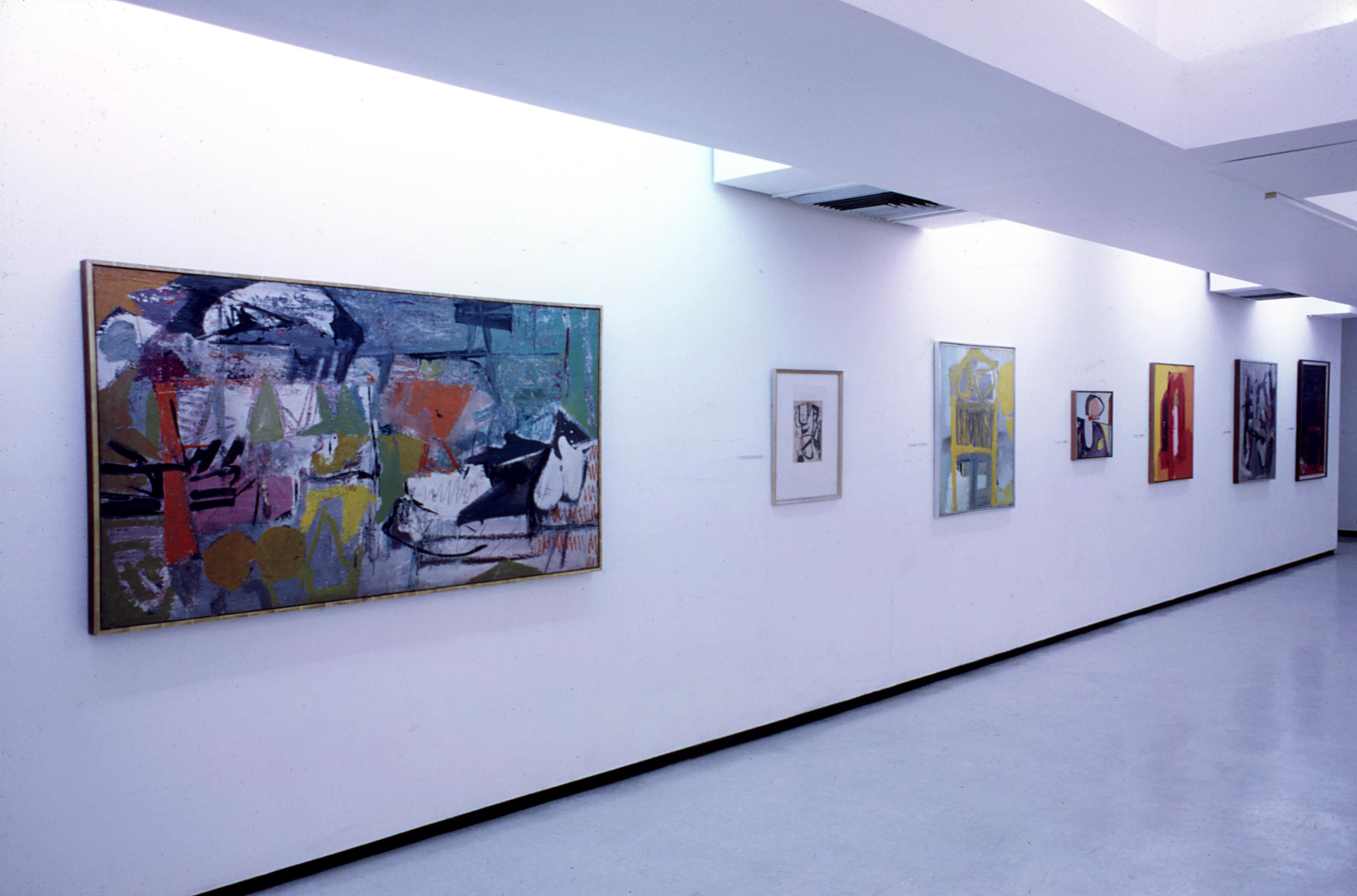 Many colorful paintings hang along a gallery wall.