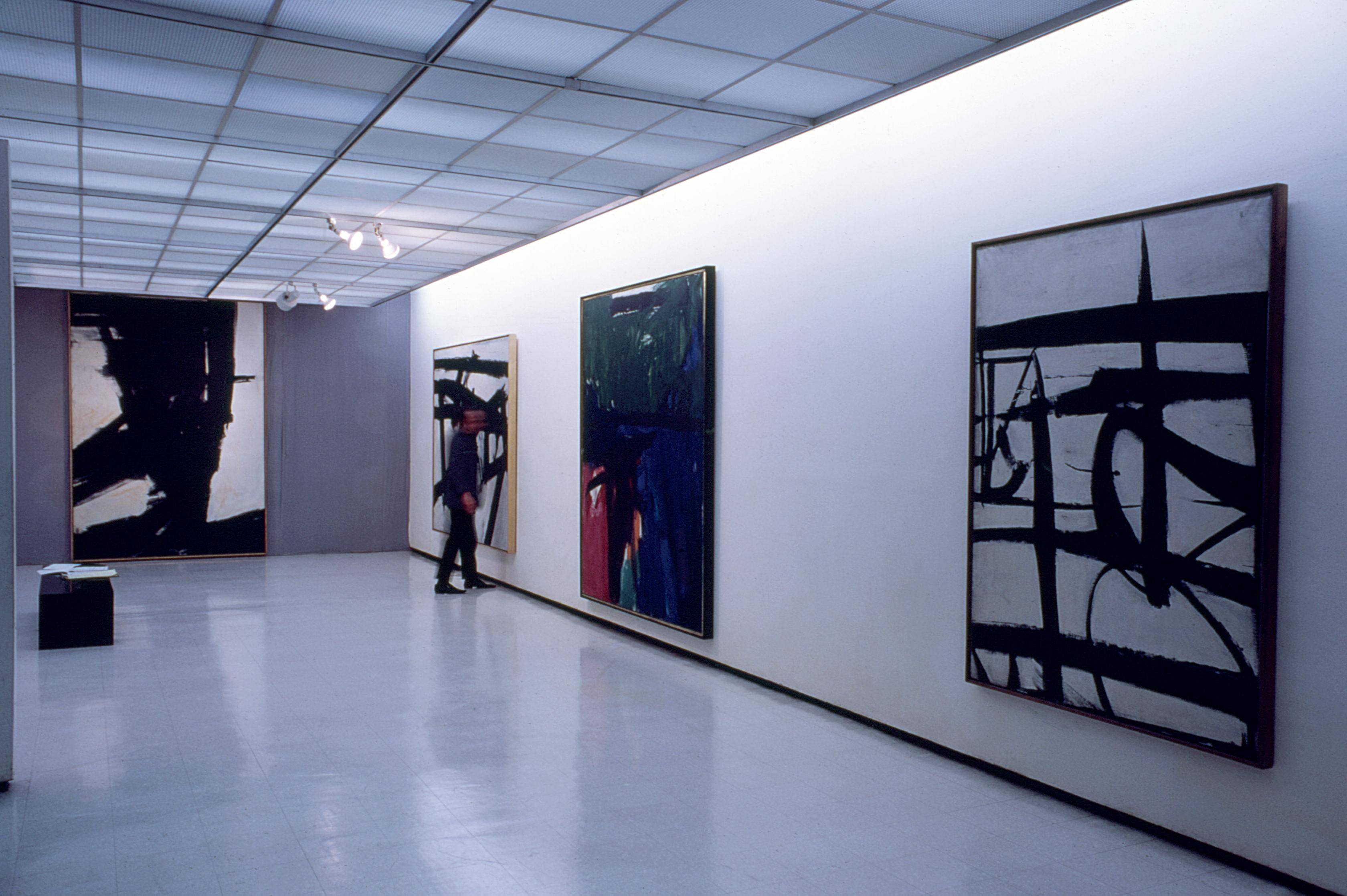 A visitor admires four large paintings hanging along a gallery wall.