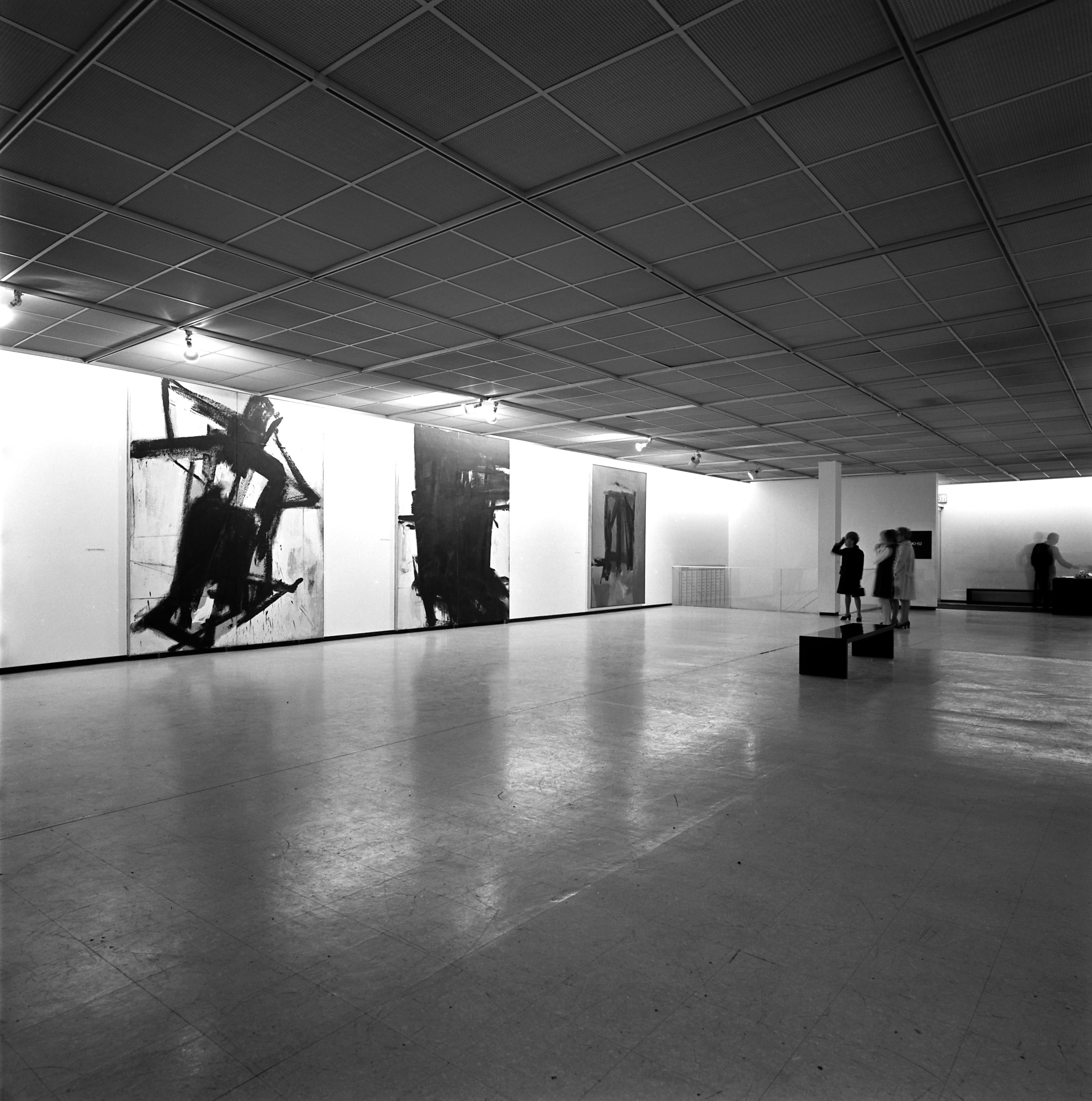 Visitors admire three large black and white paintings hanging against a gallery wall.
