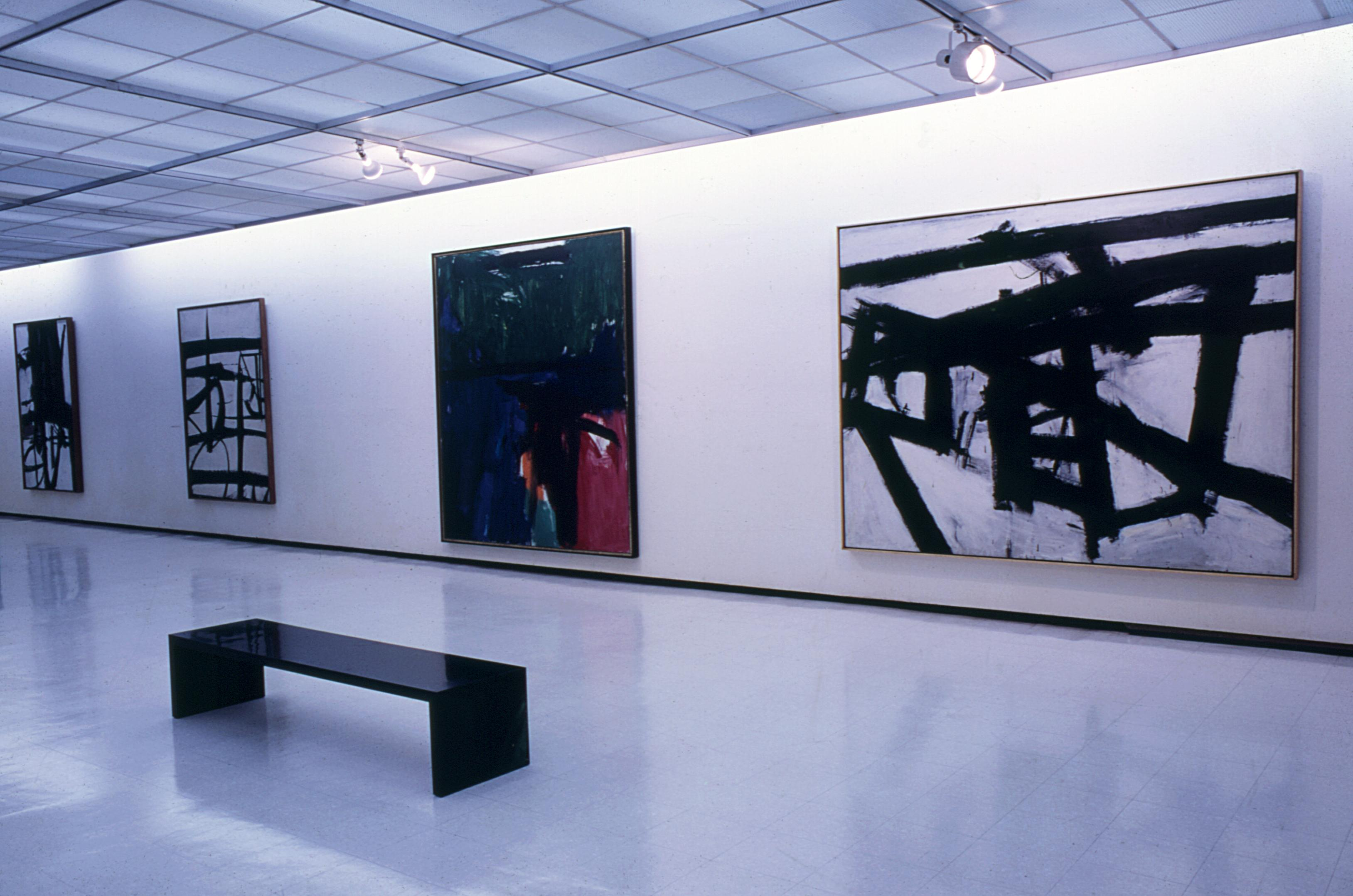 Three black and white and one multicolored paintings hang along a gallery wall.
