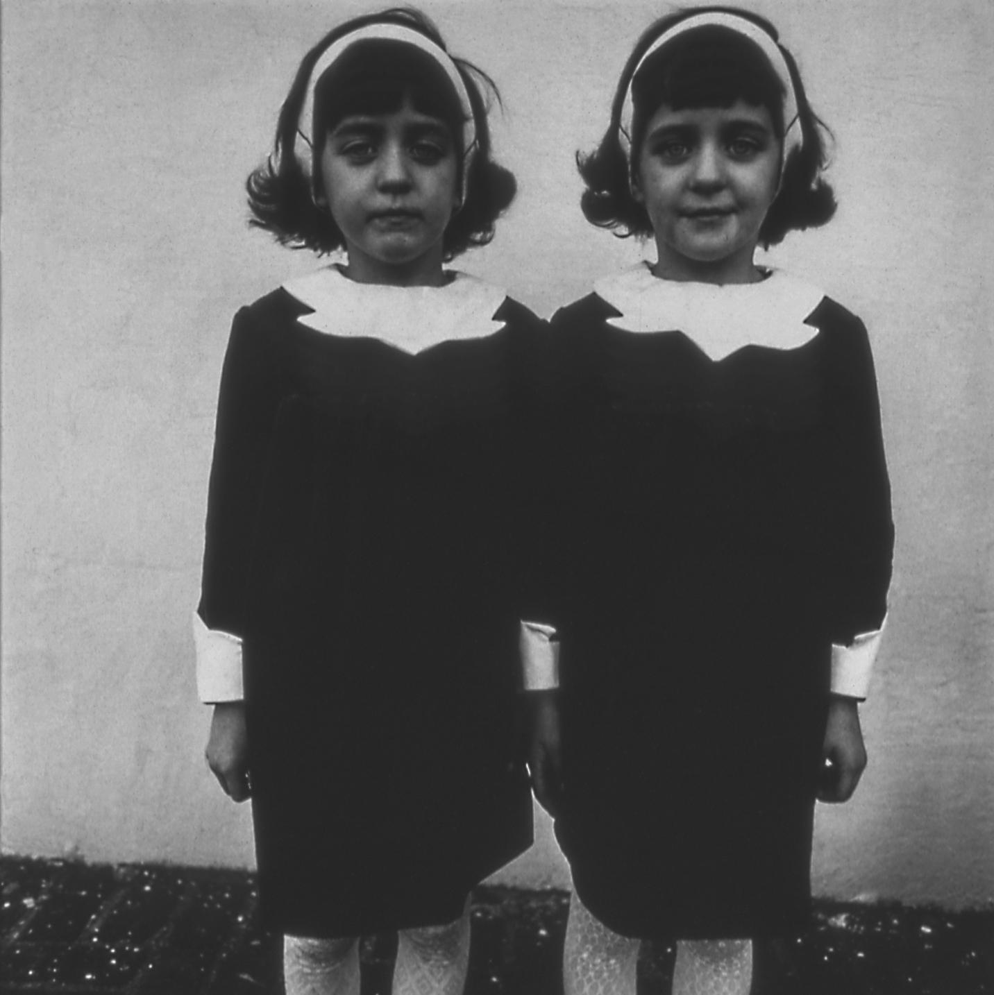 A black-and-white portrait of twins standing shoulder to shoulder. The twins are adorned in identical black dresses with white collars, white headbands, and white stockings.