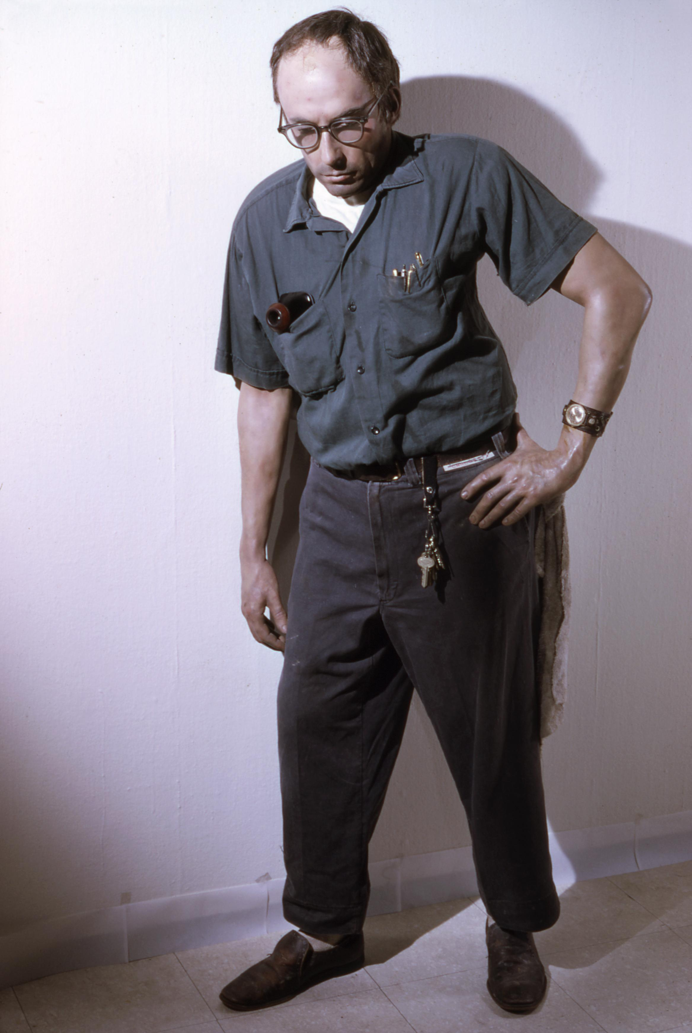 Life-size sculpture of a man dressed as a janitor, who leaning against the wall with his left hand on his hip. He has tools and pens in his shirt pockets, and keys attached to his belt loop.