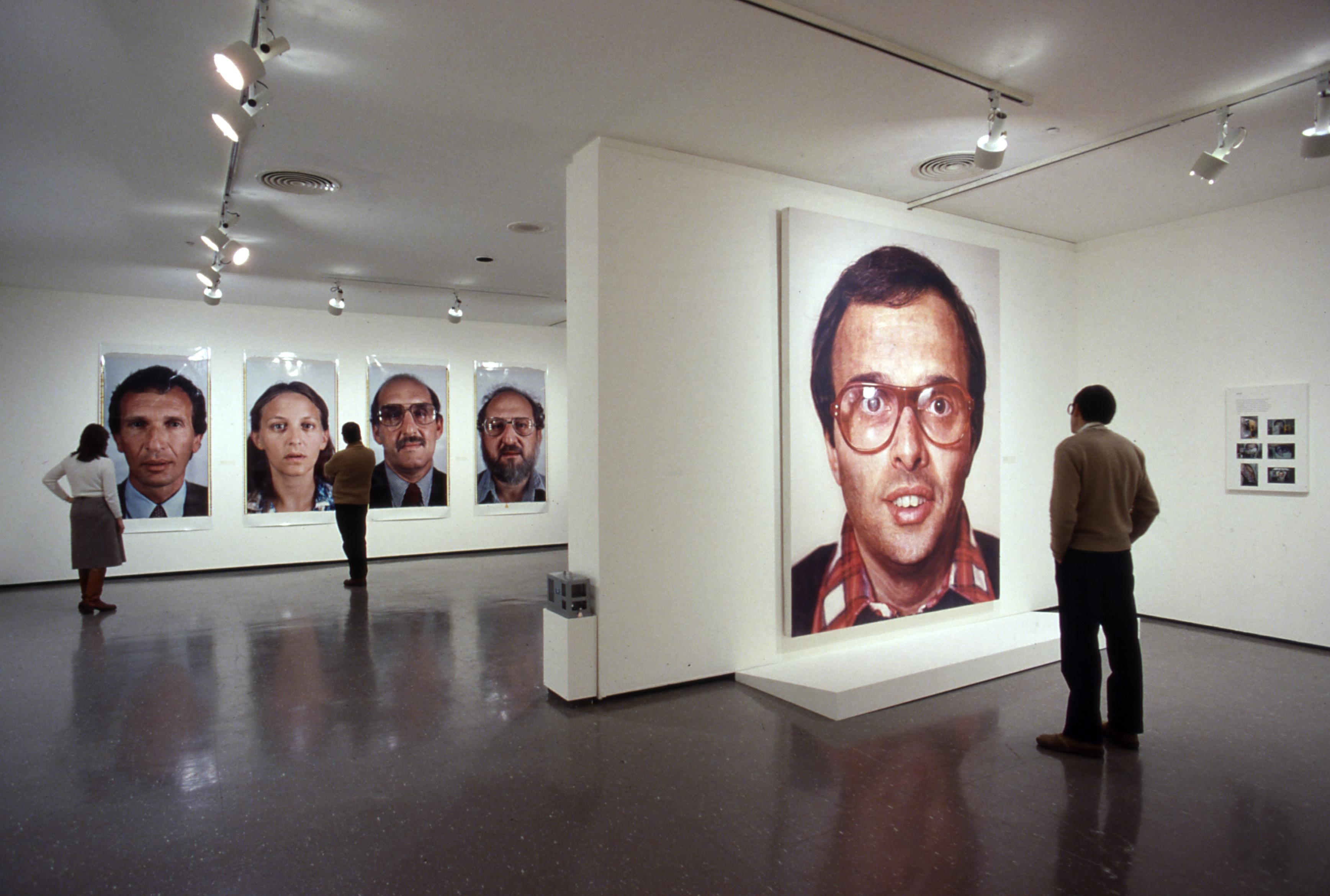 A gallery installation shows people viewing large-scale portraits of faces, four in the rear and one in the foreground.