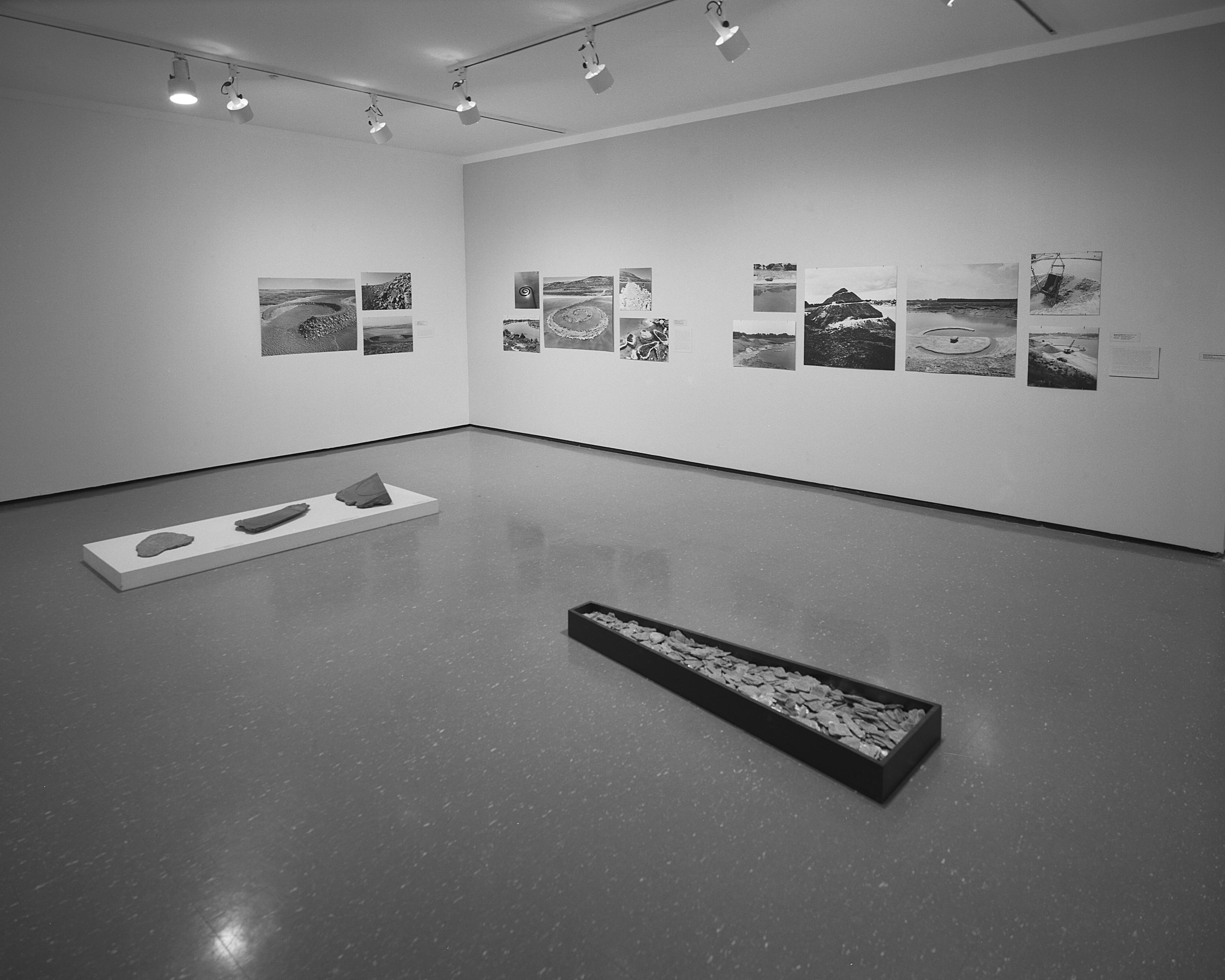 Black-and-white installation view of photographs and two sculptures that feature rocks