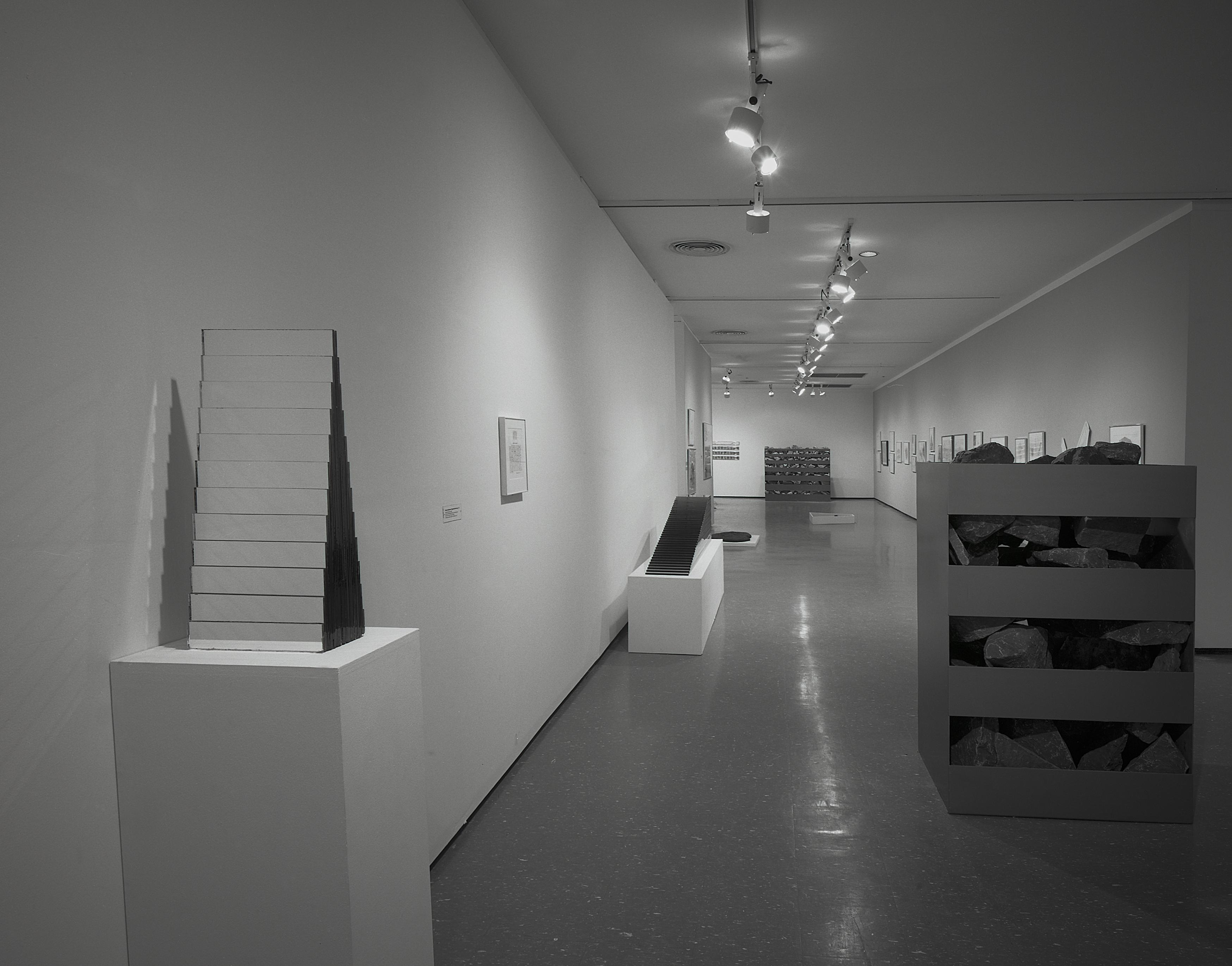 Black-and-white installation view of sculptures, including a stepped pyramid form and a crate-like sculpture filled with rocks
