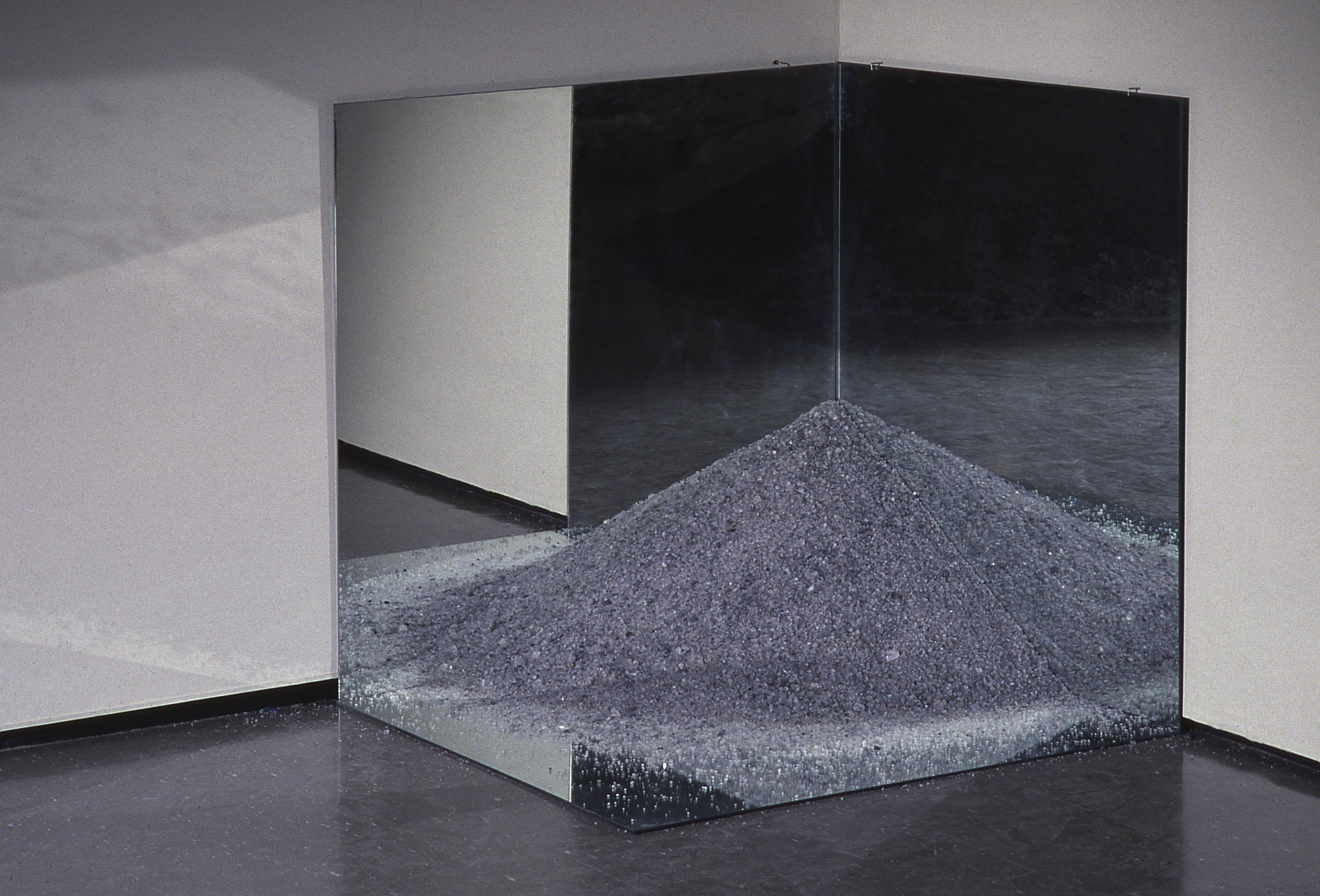 A sculpture composed of mirrors and a mound of sand appears in the corner of an art installation.