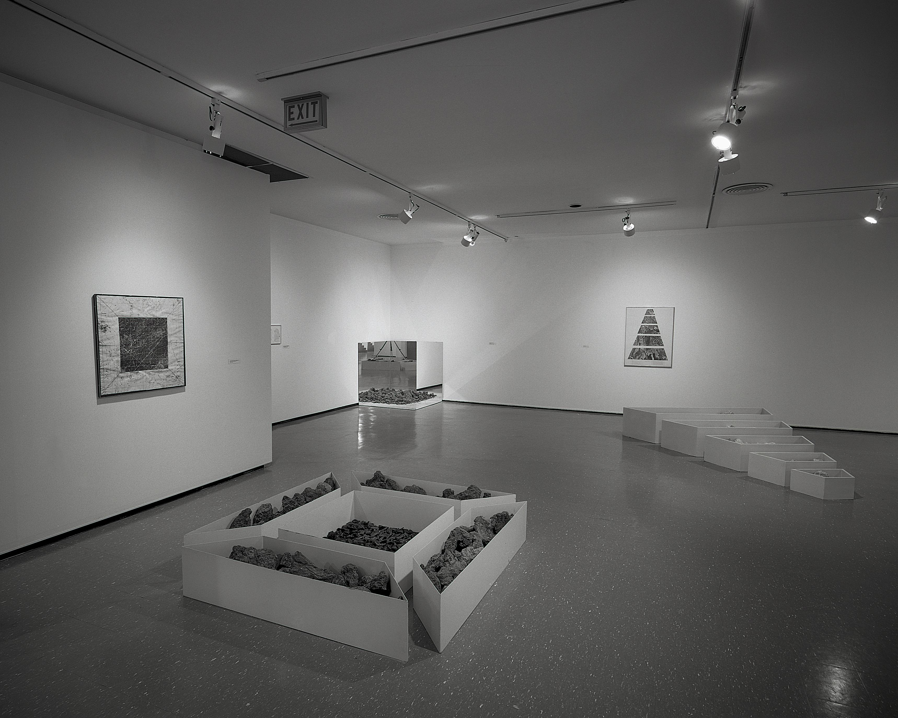 A black-and-white installation view shows photographs and sculptures made of geometric containers filled with stones.