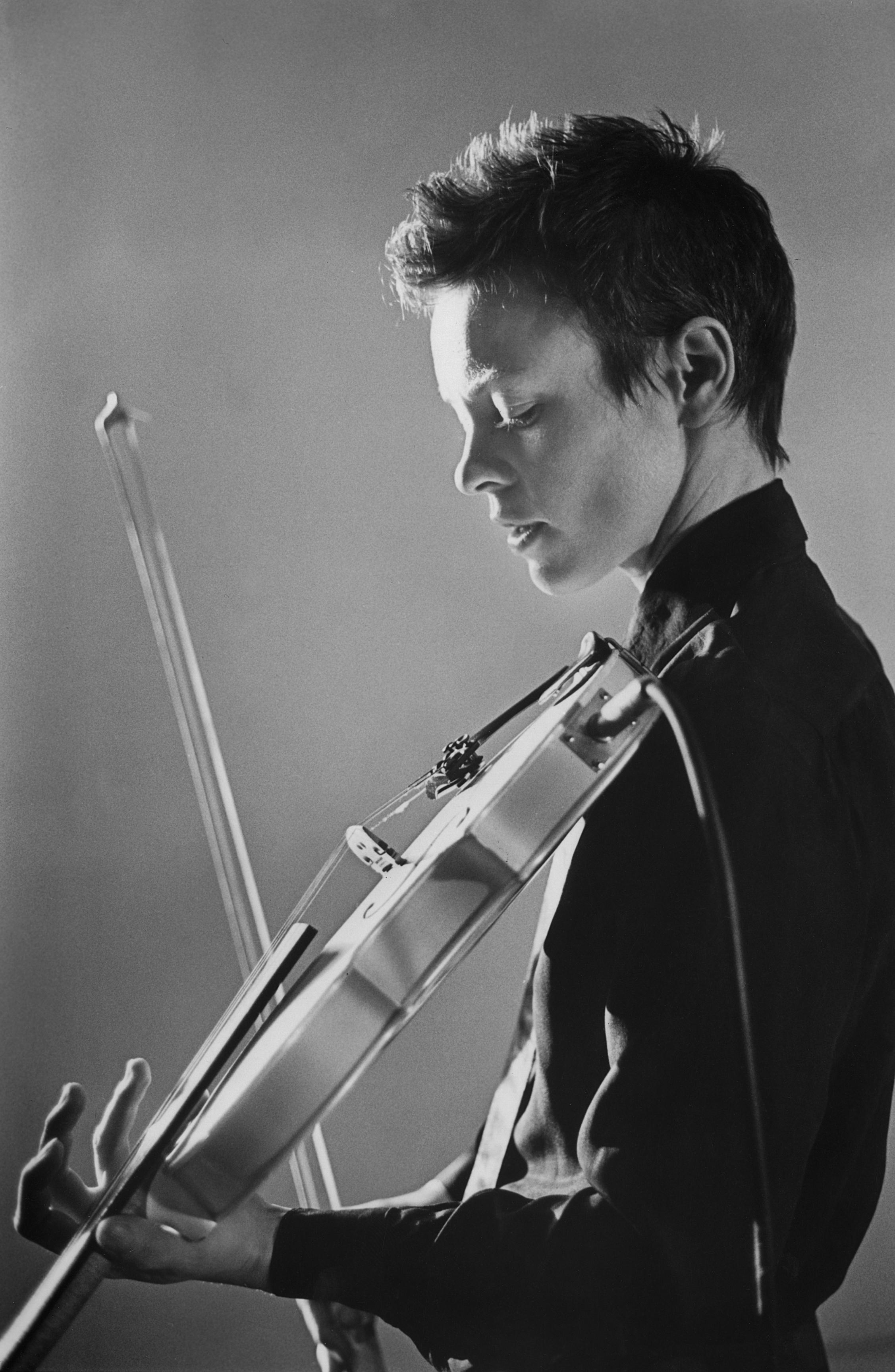 A black-and-white photograph of a youthful person with eyes closed holds a violin and bow, ready to play