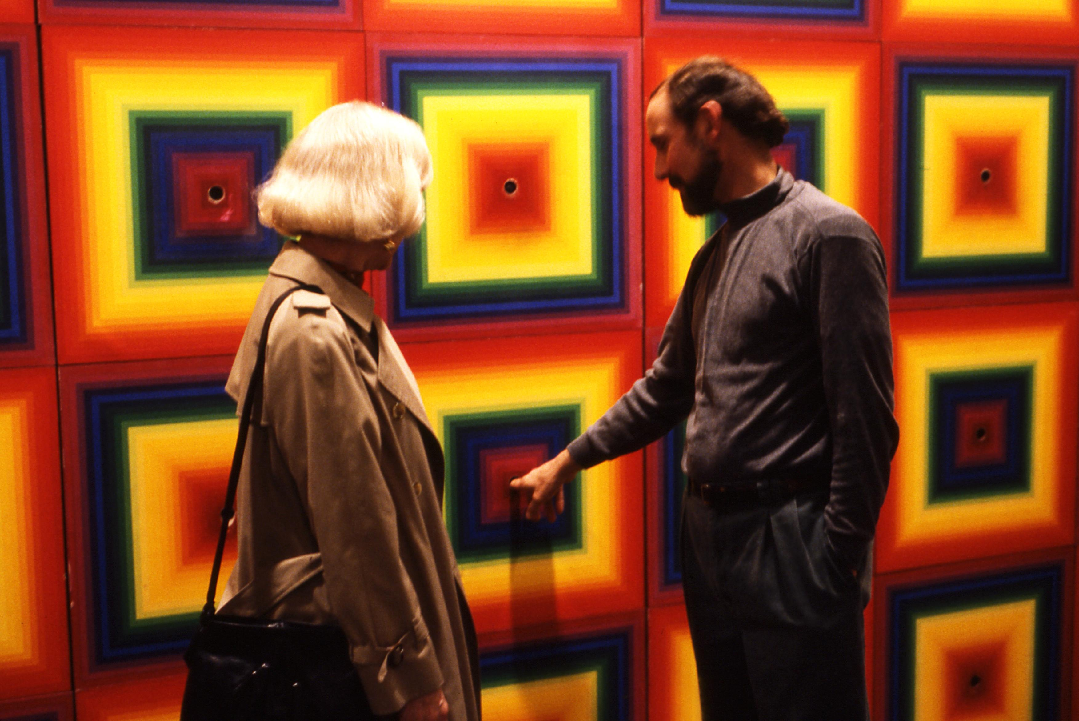 A man and a woman stand in front of a wall with a colorful, square, radial gradients with holes at the center of each. The man has finger in one hole.