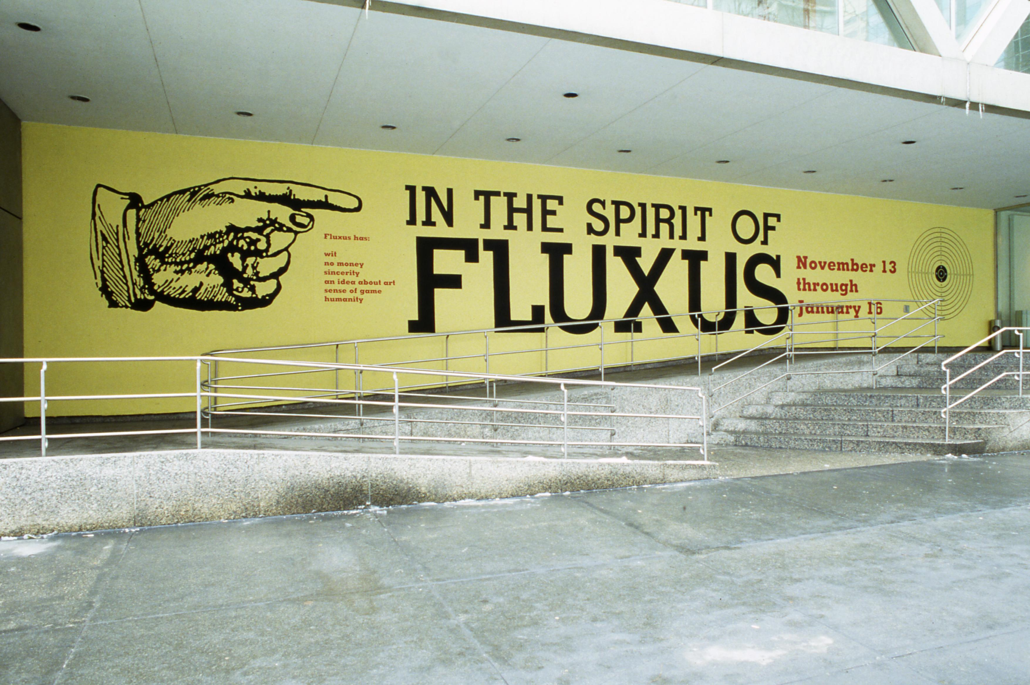 """A photograph of the MCA's former location on Ontario street with a banner that shows a large illustrated hand pointing at large text """"IN THE SPIRIT OF FLUXUS."""""""