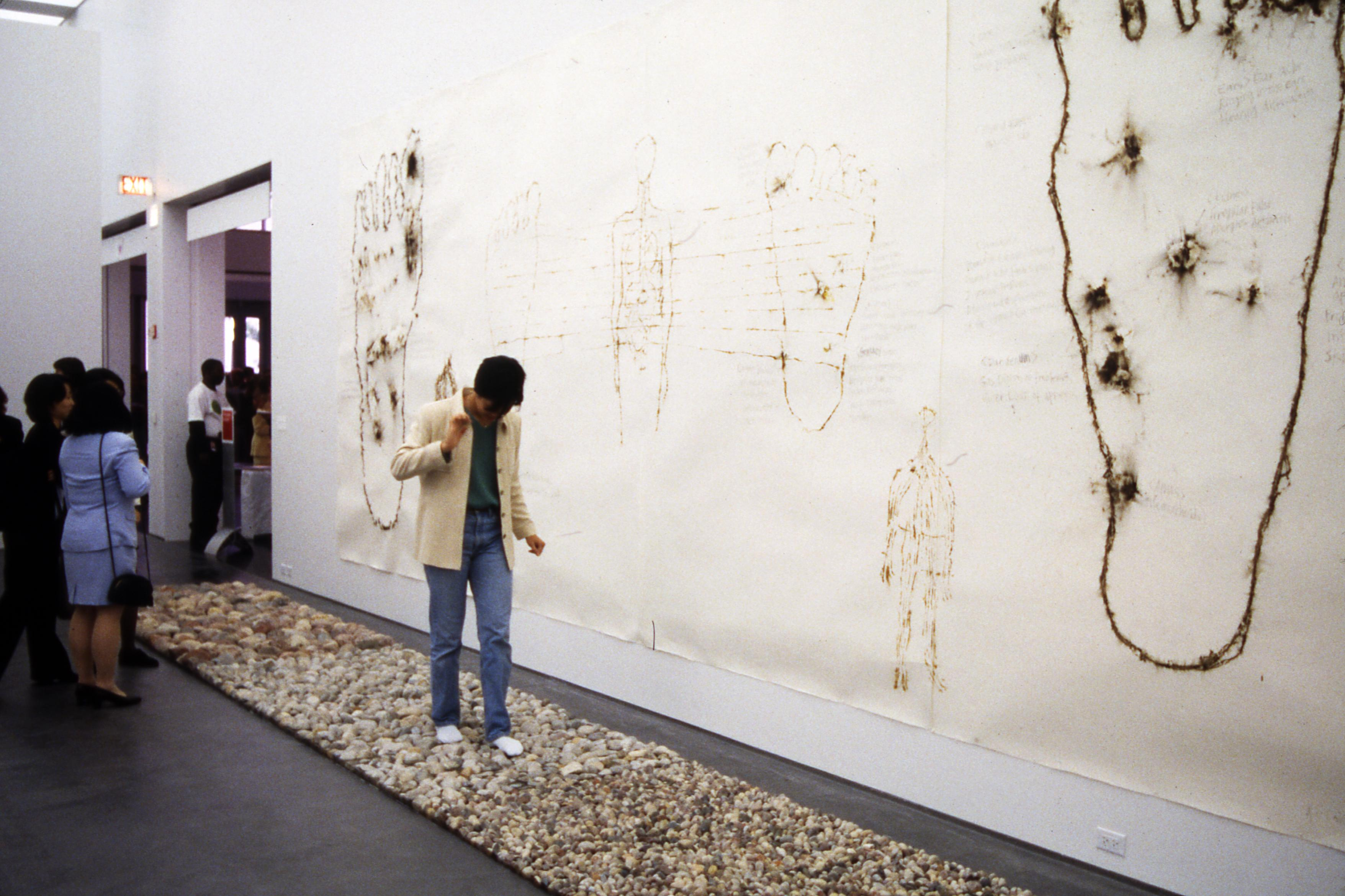A man walks tentatively across a rectangular stone path installed in a gallery. On the wall beside him are images of feet which have been punctured.