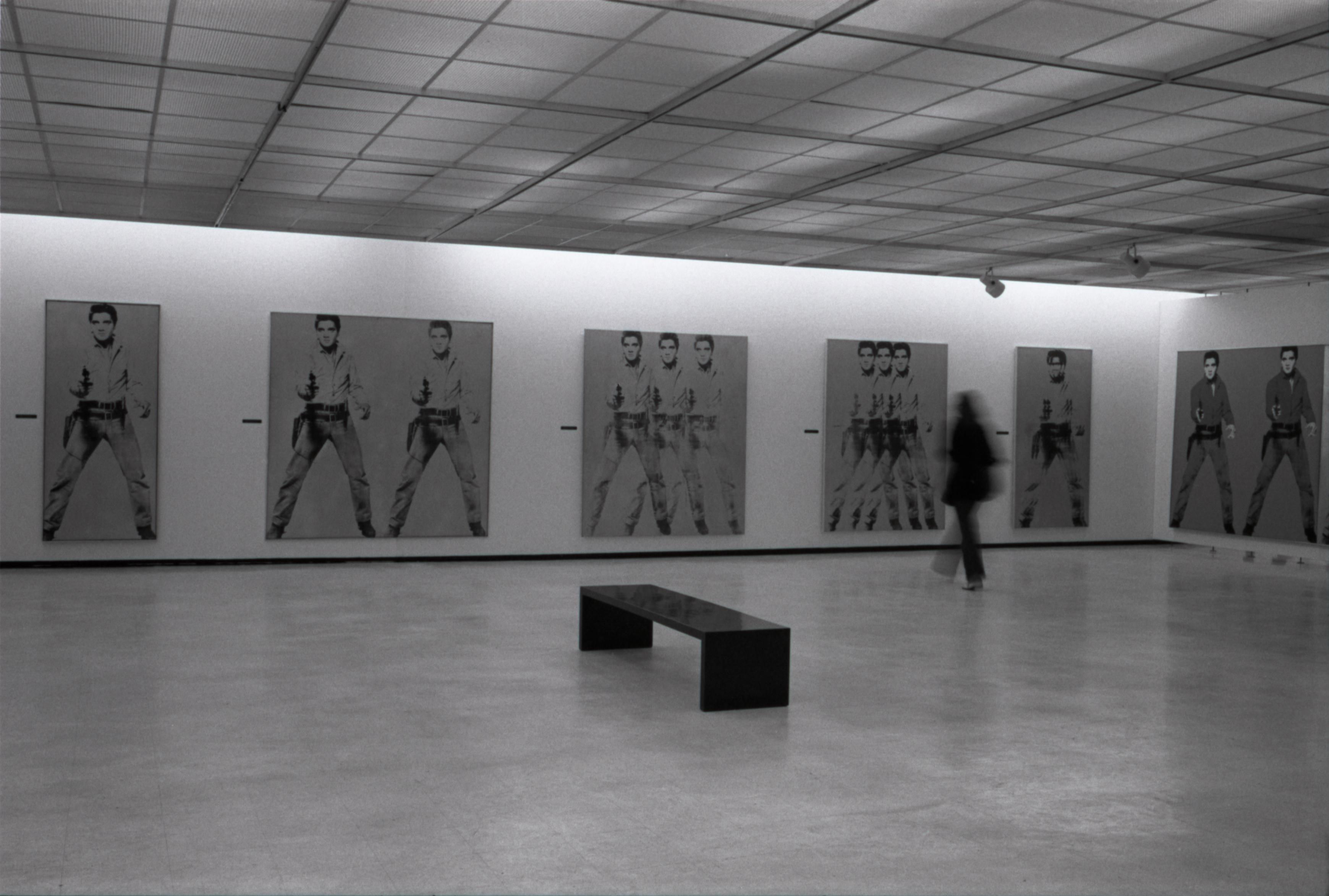 A black-and-white photograph of a gallery with several large paintings of Elvis Presley with dark hair in Western clothing holding a handgun. A black bench sits in the center of the room. A blurry person moves in the gallery.