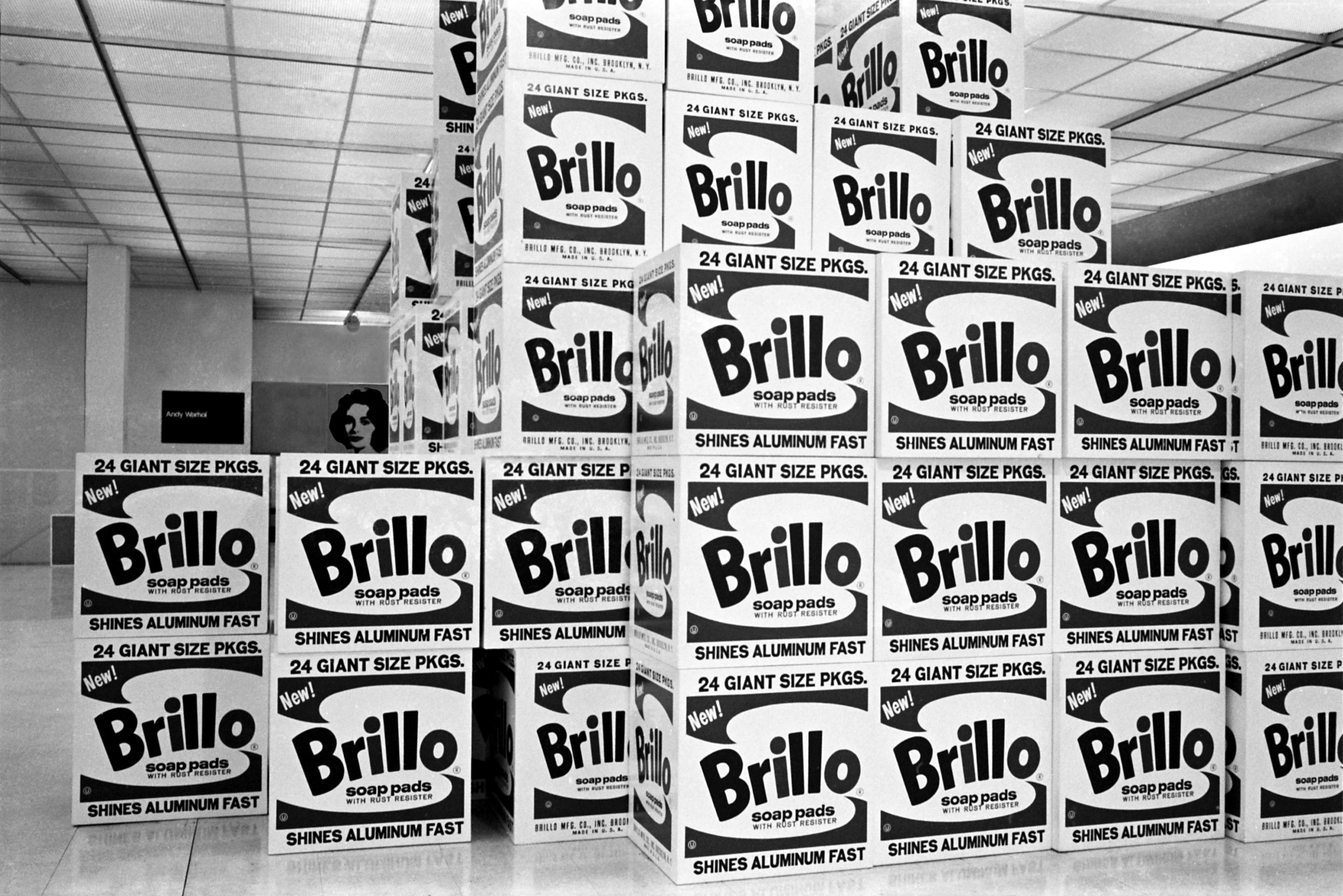 A black-and-white photo of a bunch of big boxes stacked together all the way to the ceiling.