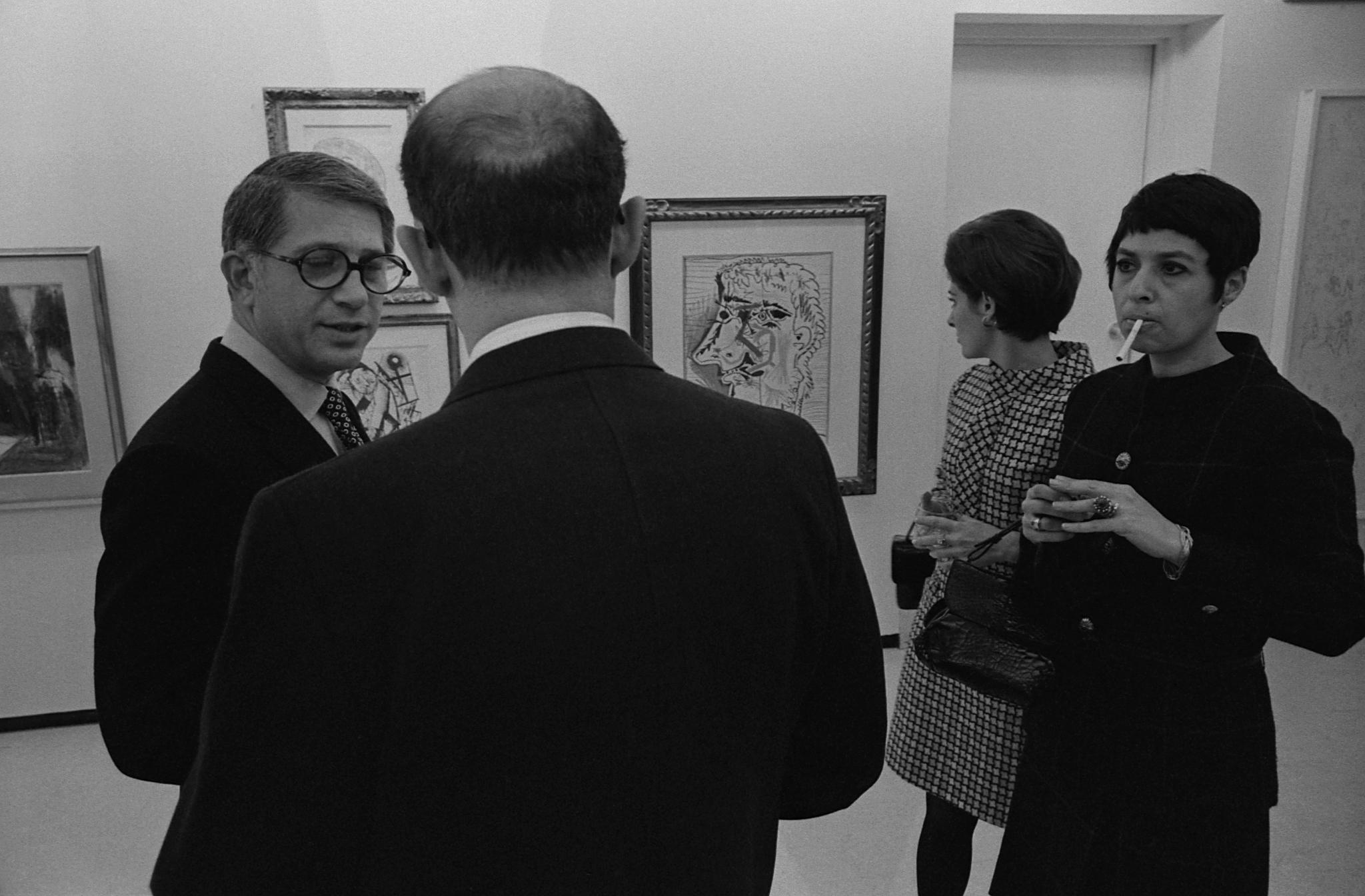 Black-and-white photograph of four people in 70s clothing discussing art in a gallery