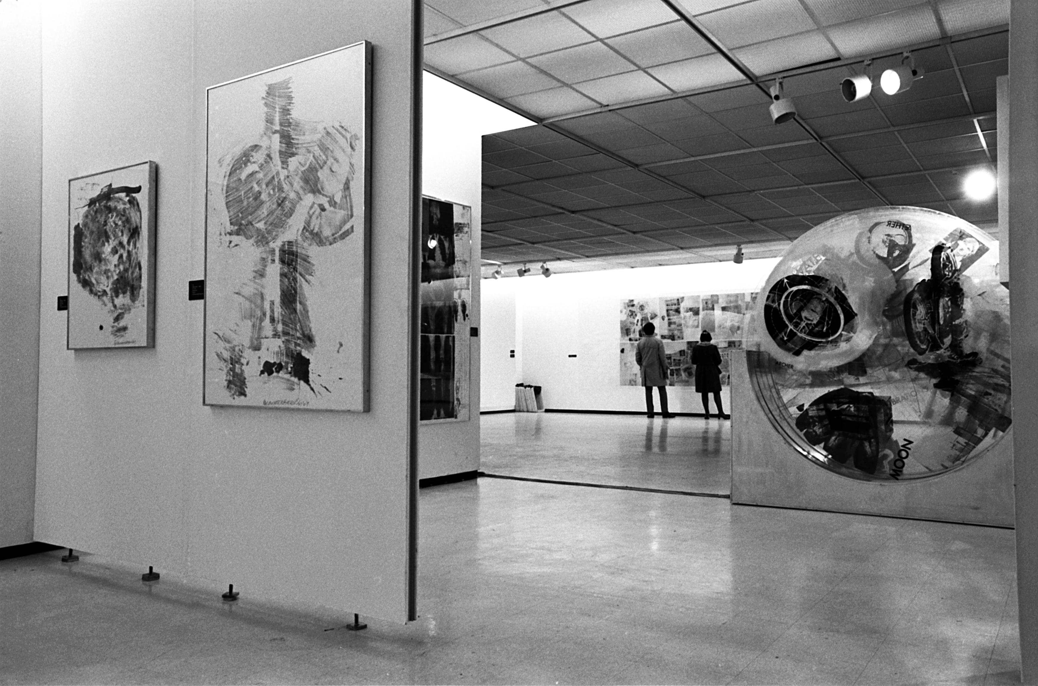 A black-and-white photo of a partial installation view shows a sculpture and multiple other graphic artworks.