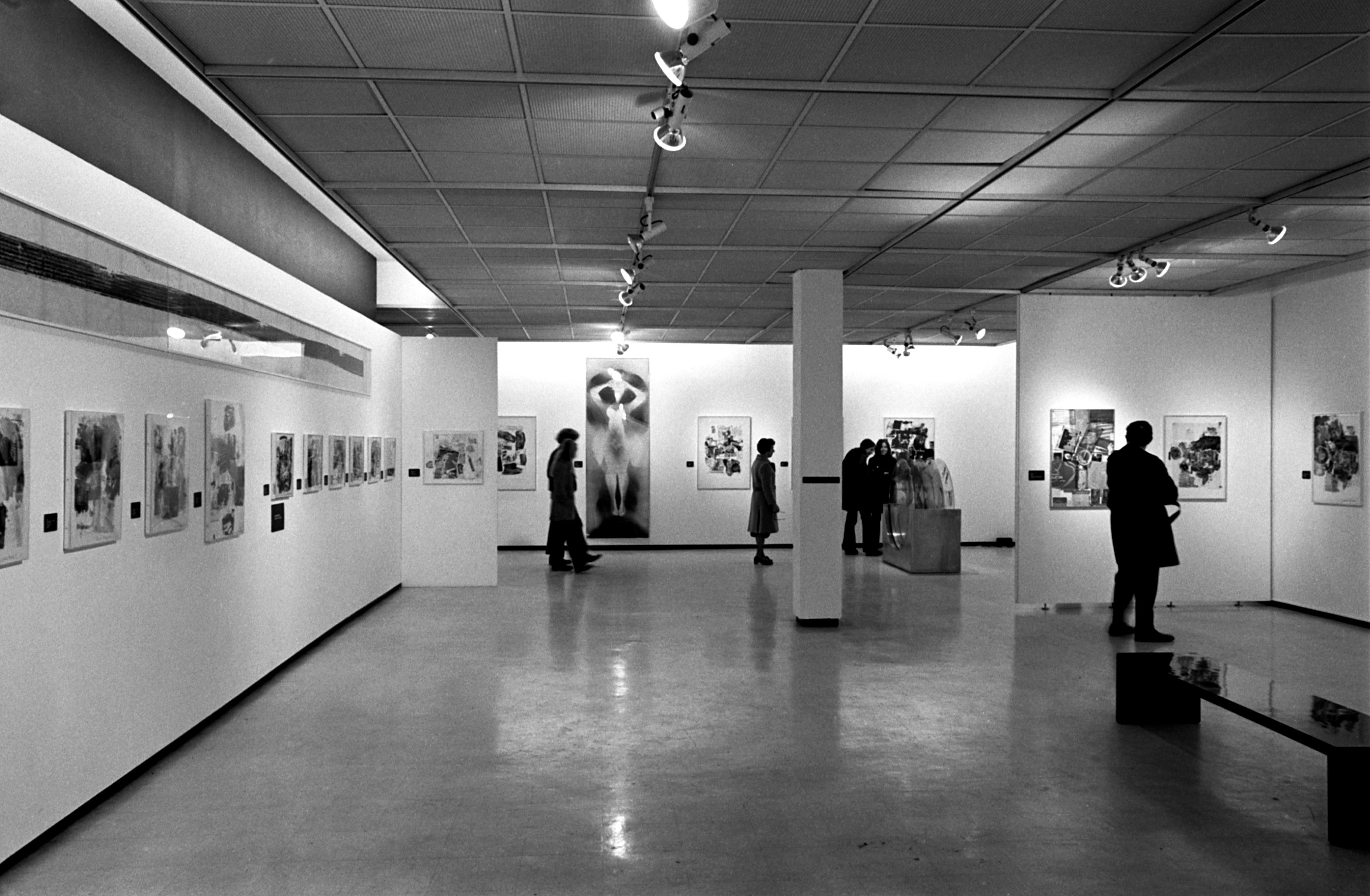 A black-and-white installation photograph of graphic artworks and visitors.