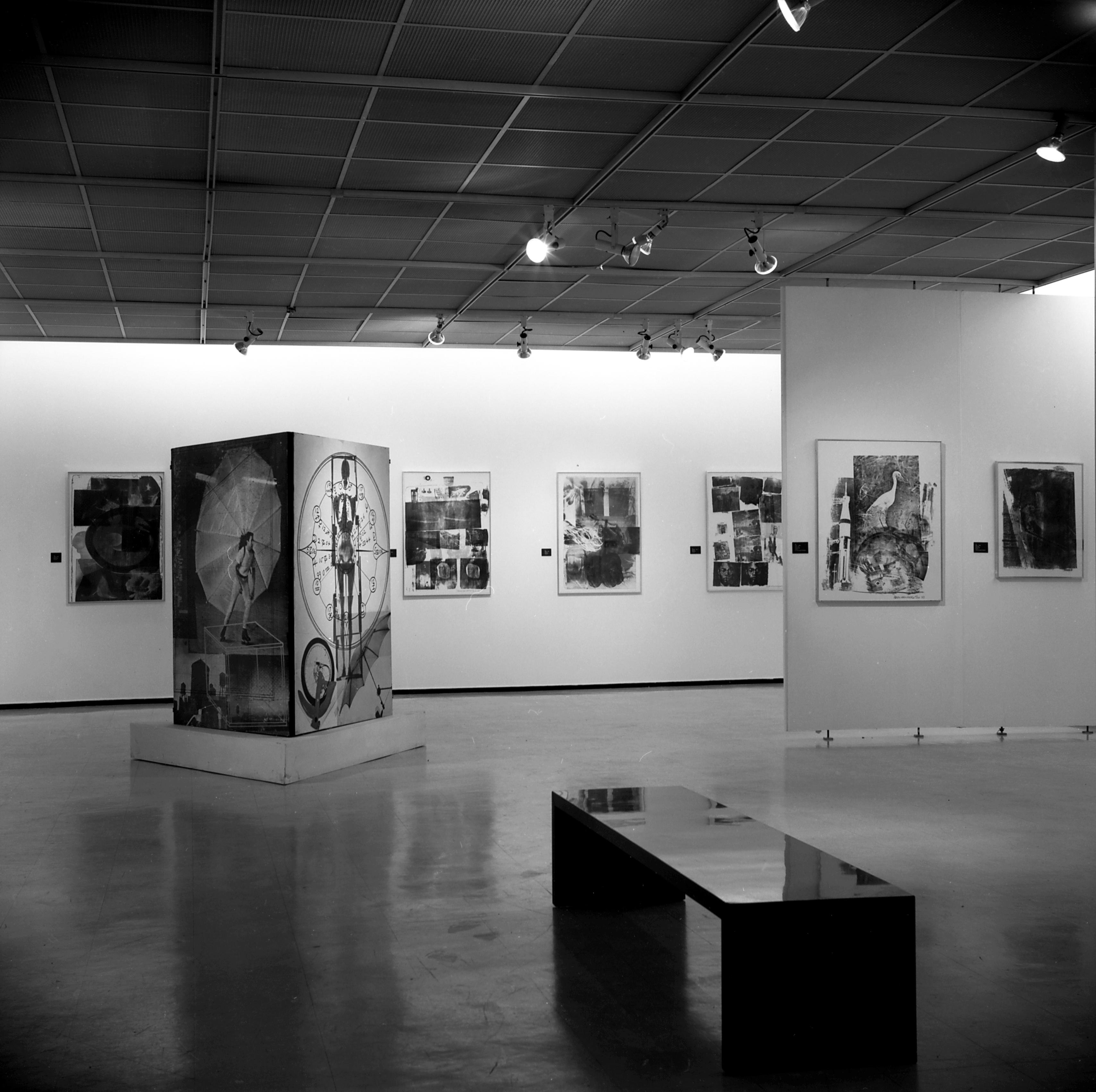 Black-and-white installation view of graphic artworks that appear collaged